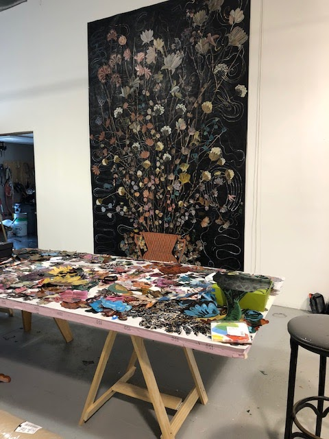 Nancy Friedemann-Sánchez at her studio in Lincoln, Nebraska. Her work table is full of the many flowers she has researched and painted, readying them to place as a collage on her canvas.