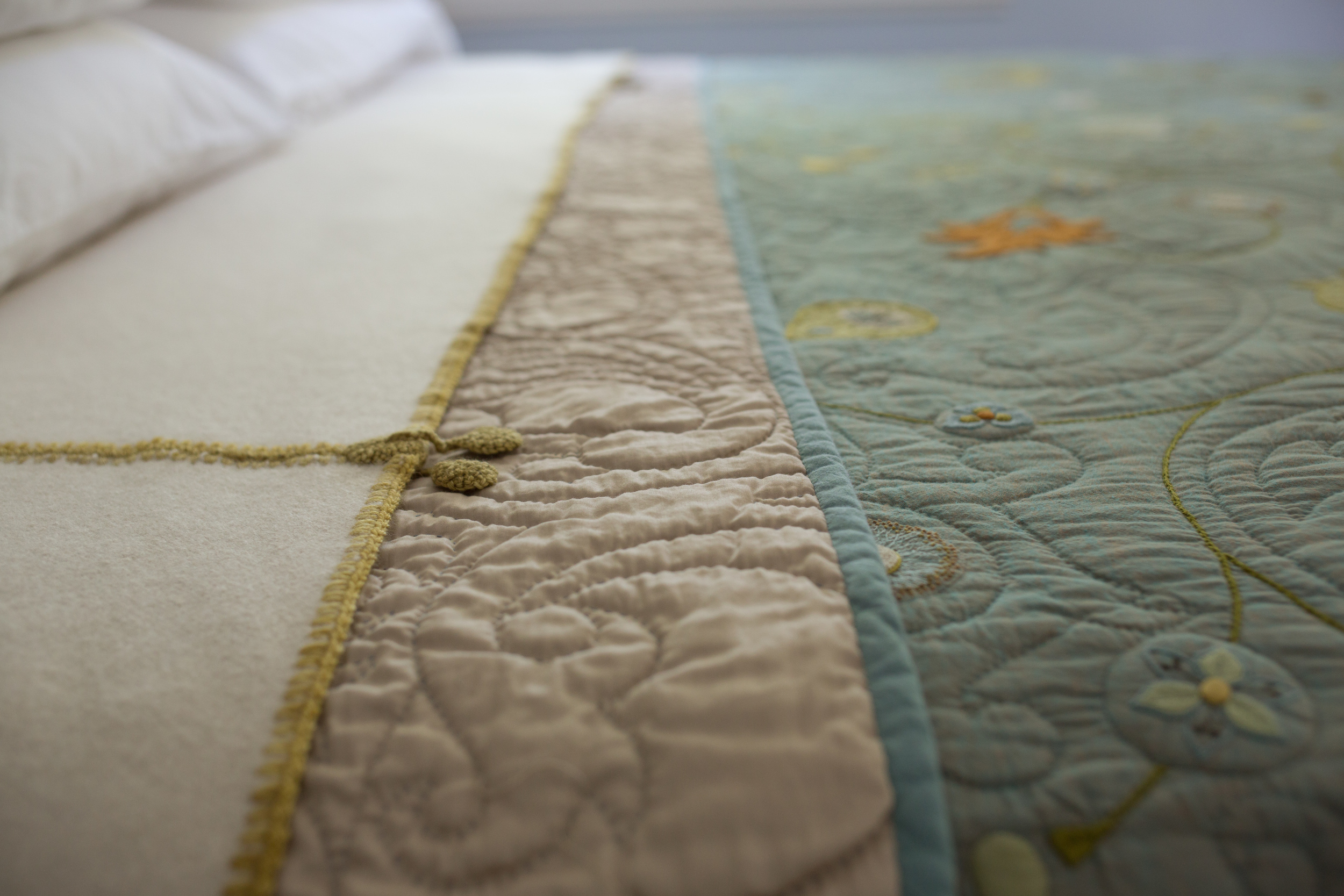View of the entwine quilt and its accompanying cashmere blanket with hand crochet border