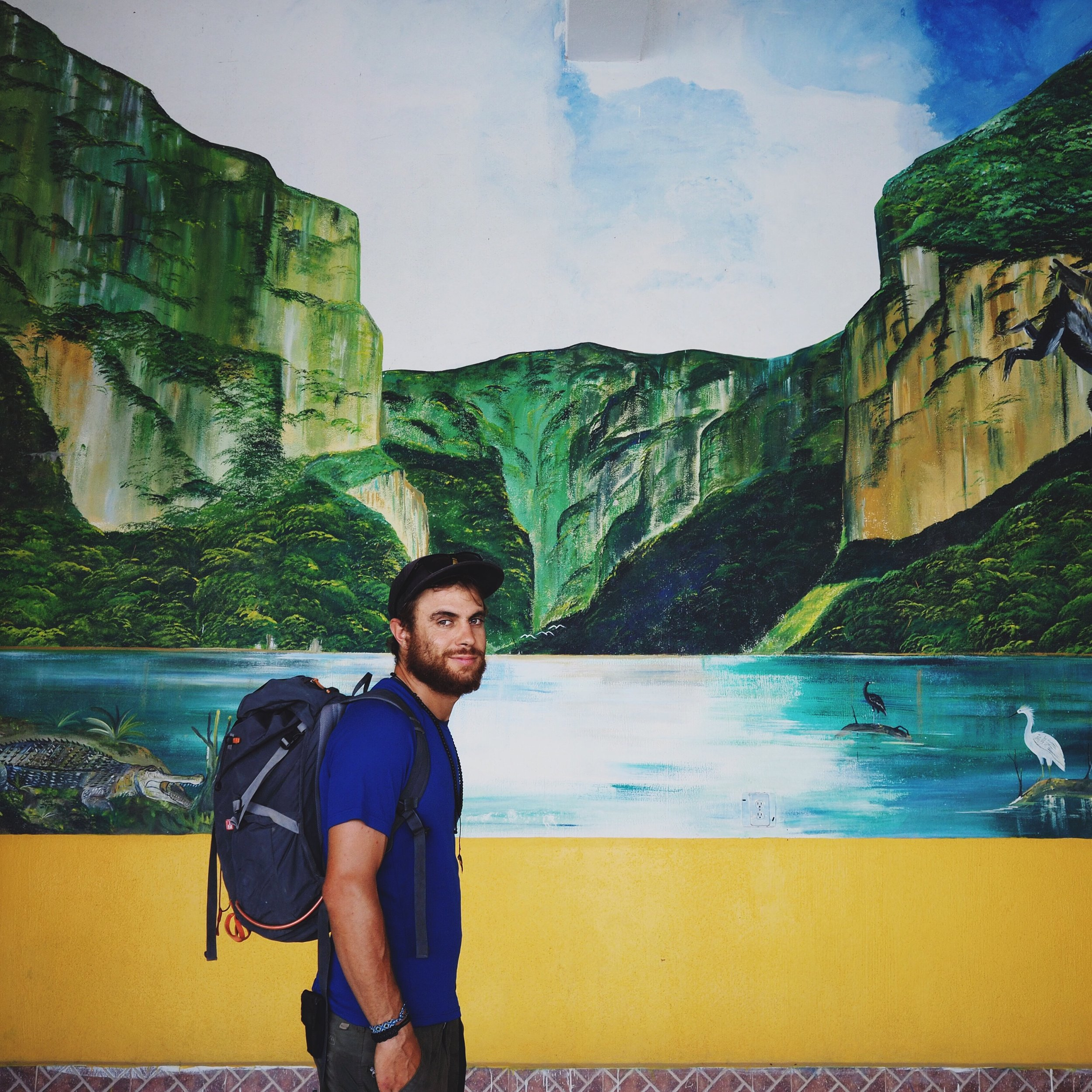 Mehedi posing in front of a painting of the iconic Cañon del Sumidero viewpoint