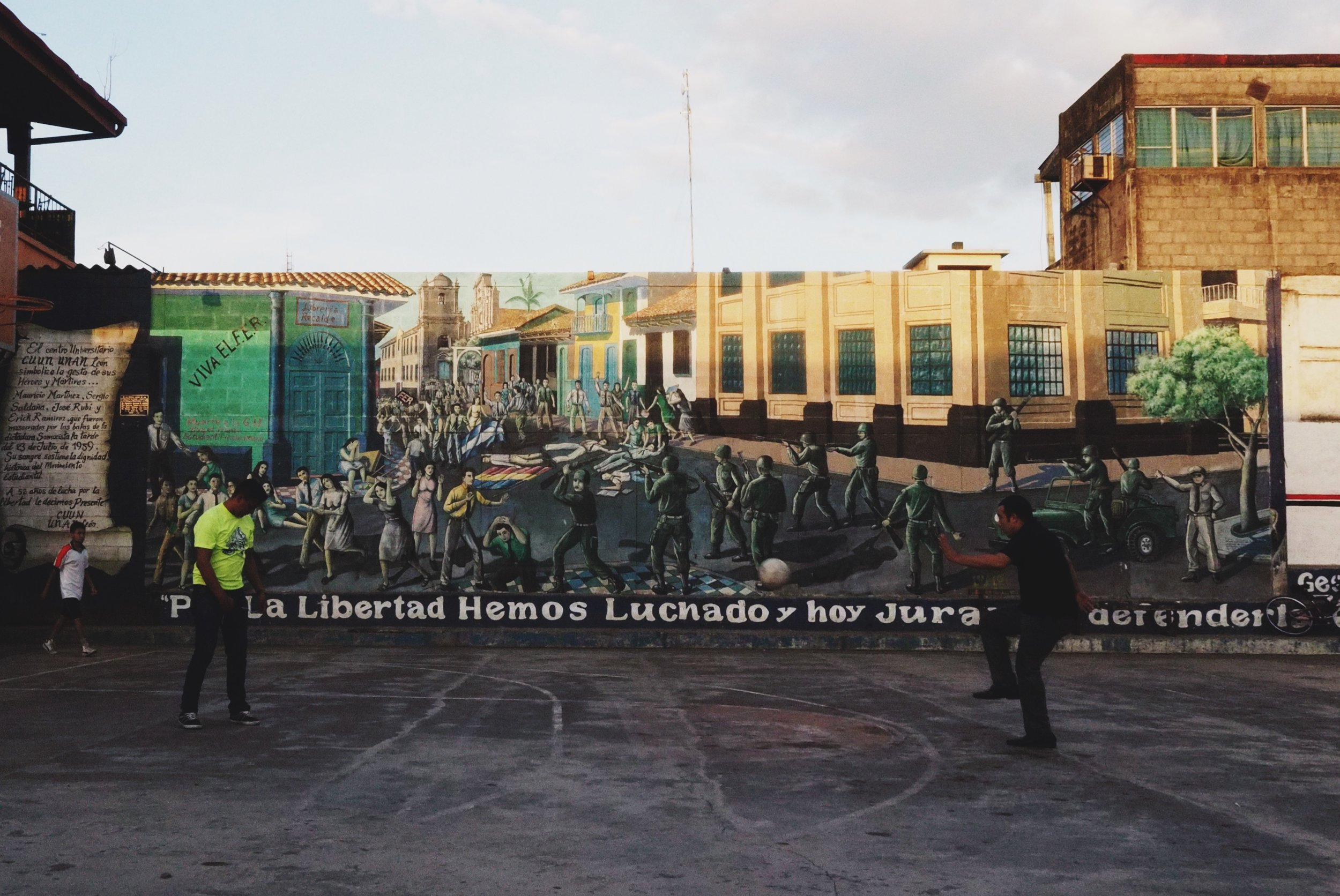"""Two young guys playing fútbol - the mural in the background reads """"para la libertad hemos luchado y hoy juras de defenderla."""" """"For liberty we have fought and today you swear to defend it"""""""
