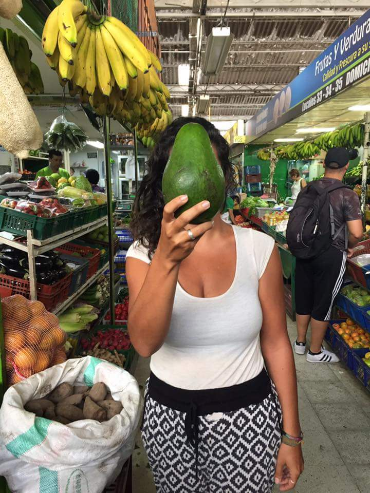 Erin admires enormous avocados in Medellín's Mercado de las Americas