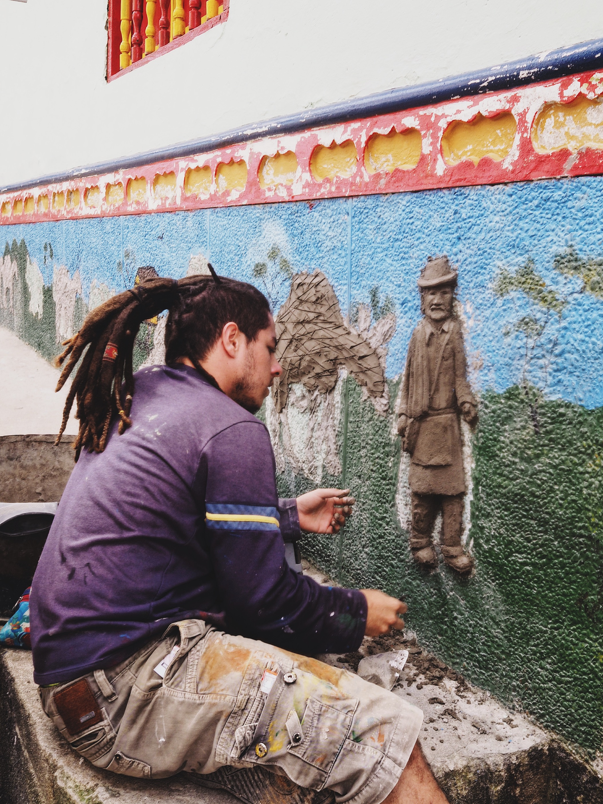 Local artist working on one of the town's facades