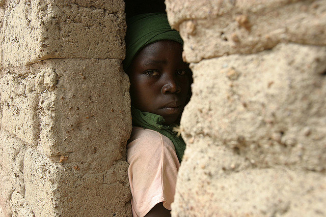Central african child peers through wall, photo by pierre holtz