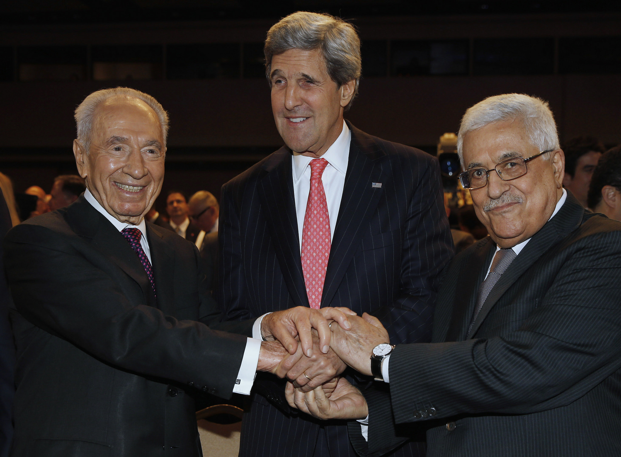 U.S. Secretary of State John Kerry (C) shakes hands with Israeli President Shimon Peres (L) and Palestinian President Mahmoud Abbas at the World Economic Forum on the Middle East and North Africa at the King Hussein Convention Centre, at the Dead Sea May 26, 2013. REUTERS/Jim Young