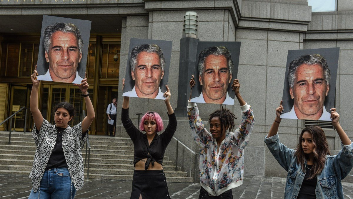 Members of a protest group called Hot Mess hold up photos of Jeffrey Epstein in front of the federal courthouse in New York on Monday. Photo Agency France Press