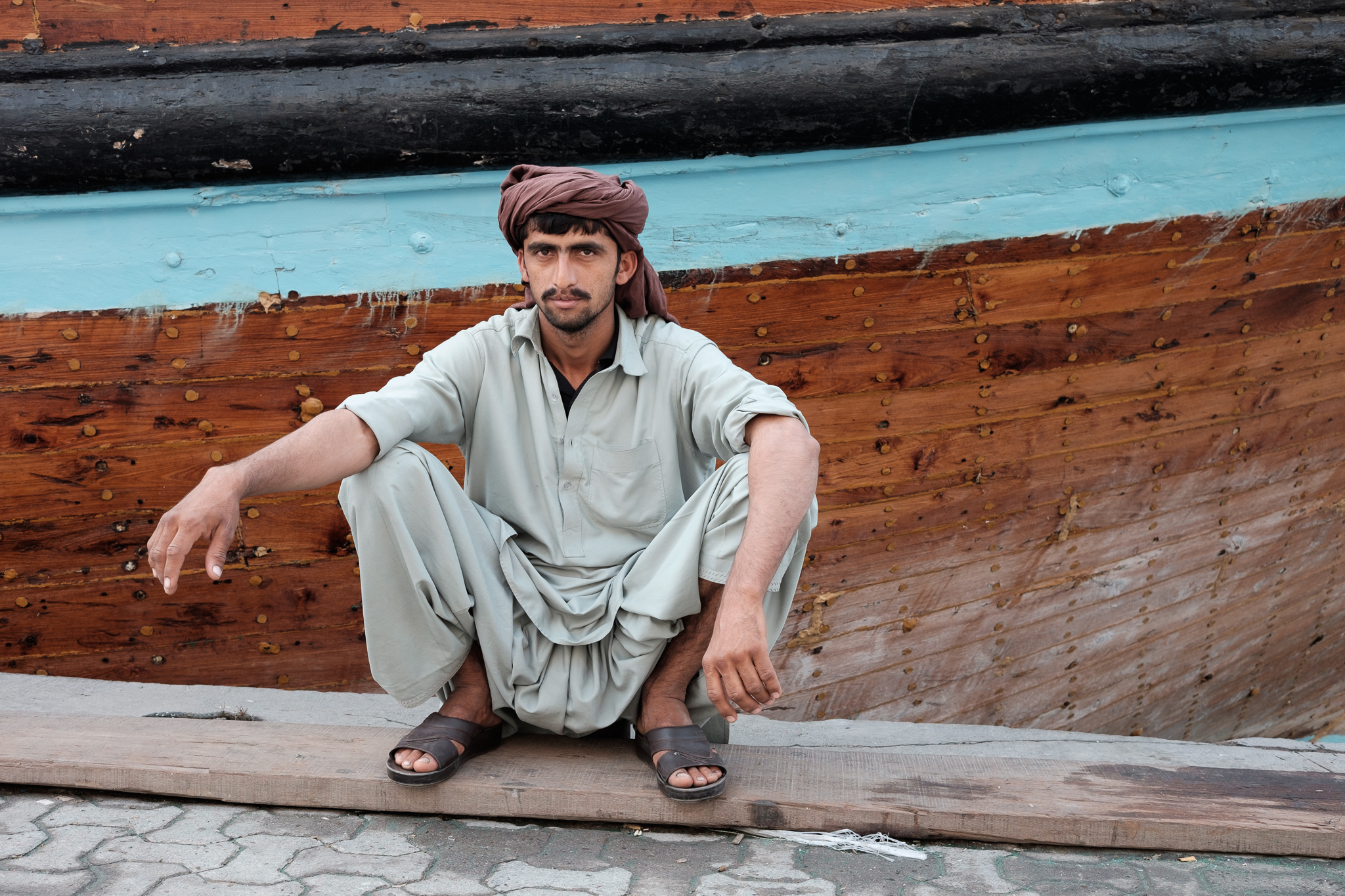 Young Pakastani man taking a break from loading goods on to a Cargo ship heading for Iran
