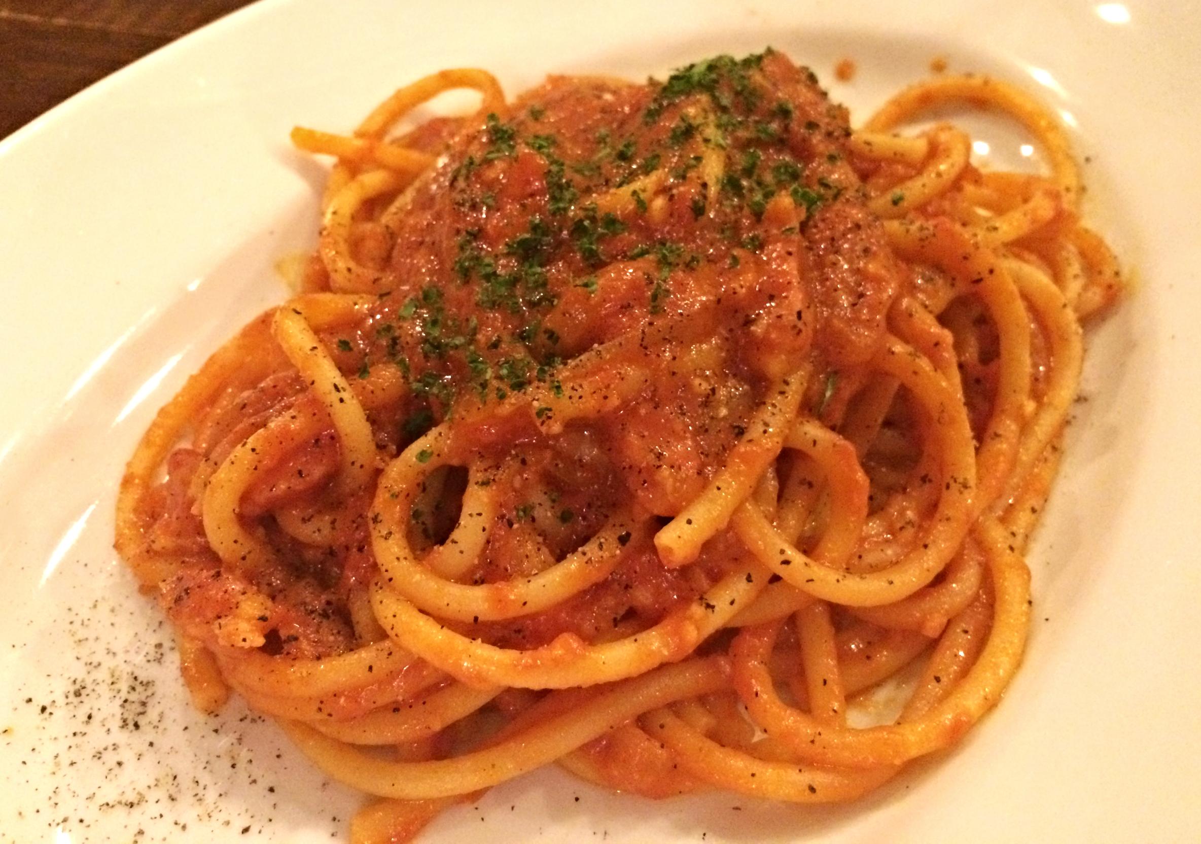 超人気   ブッカティーニ アマトリチャーナ   ゴンブト麺のブカティーニで、パンチェッタの風味の効いたトマトソースが美味しい超人気パスタです。  ブカティーニは中に穴の開いている太長い麺。それに濃厚なトマトソースが絡まって、一度食べたら病みつきの味。リピーター続出です!