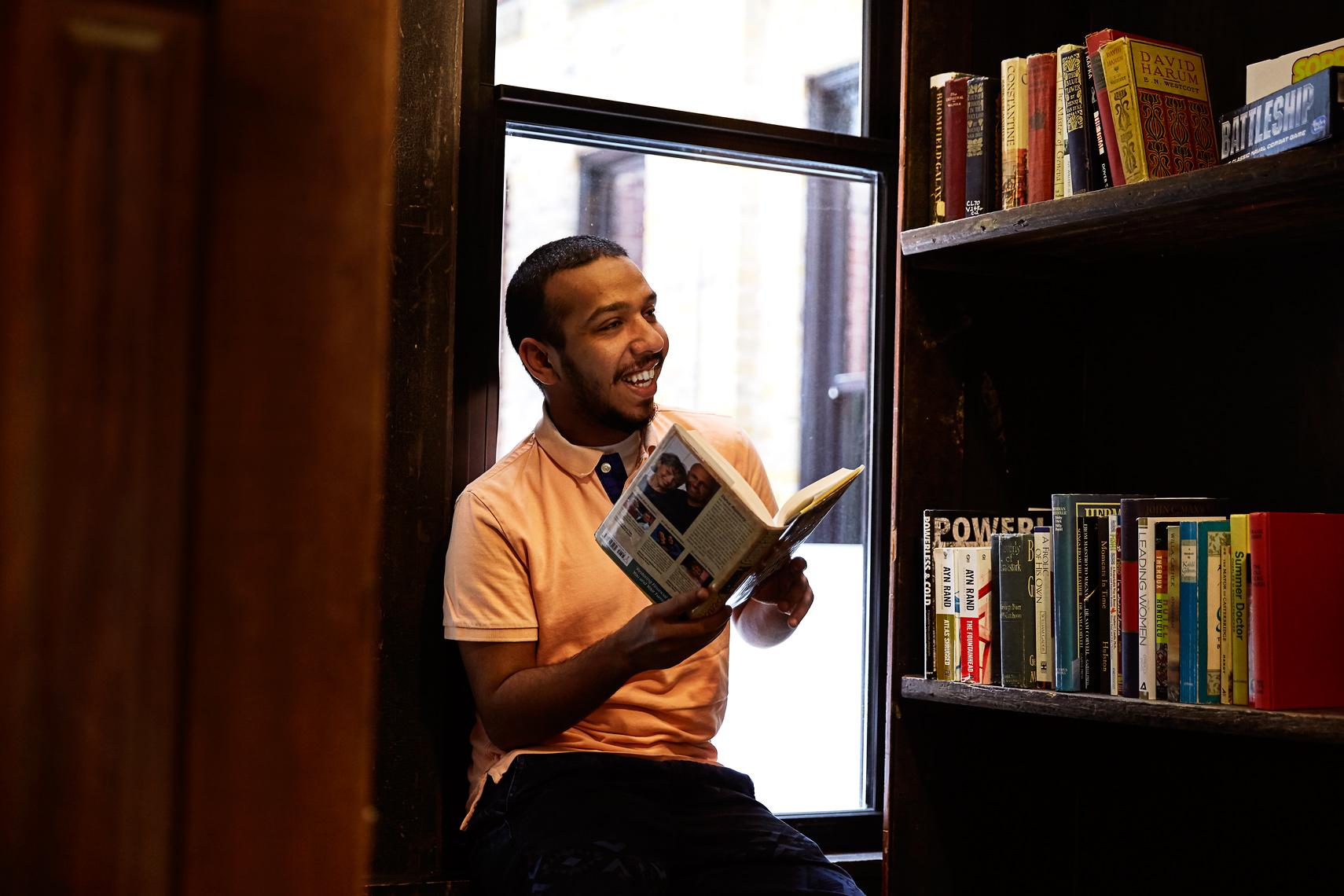 Reside  Park East Resident enjoying the open bookshelf at The Sterling.
