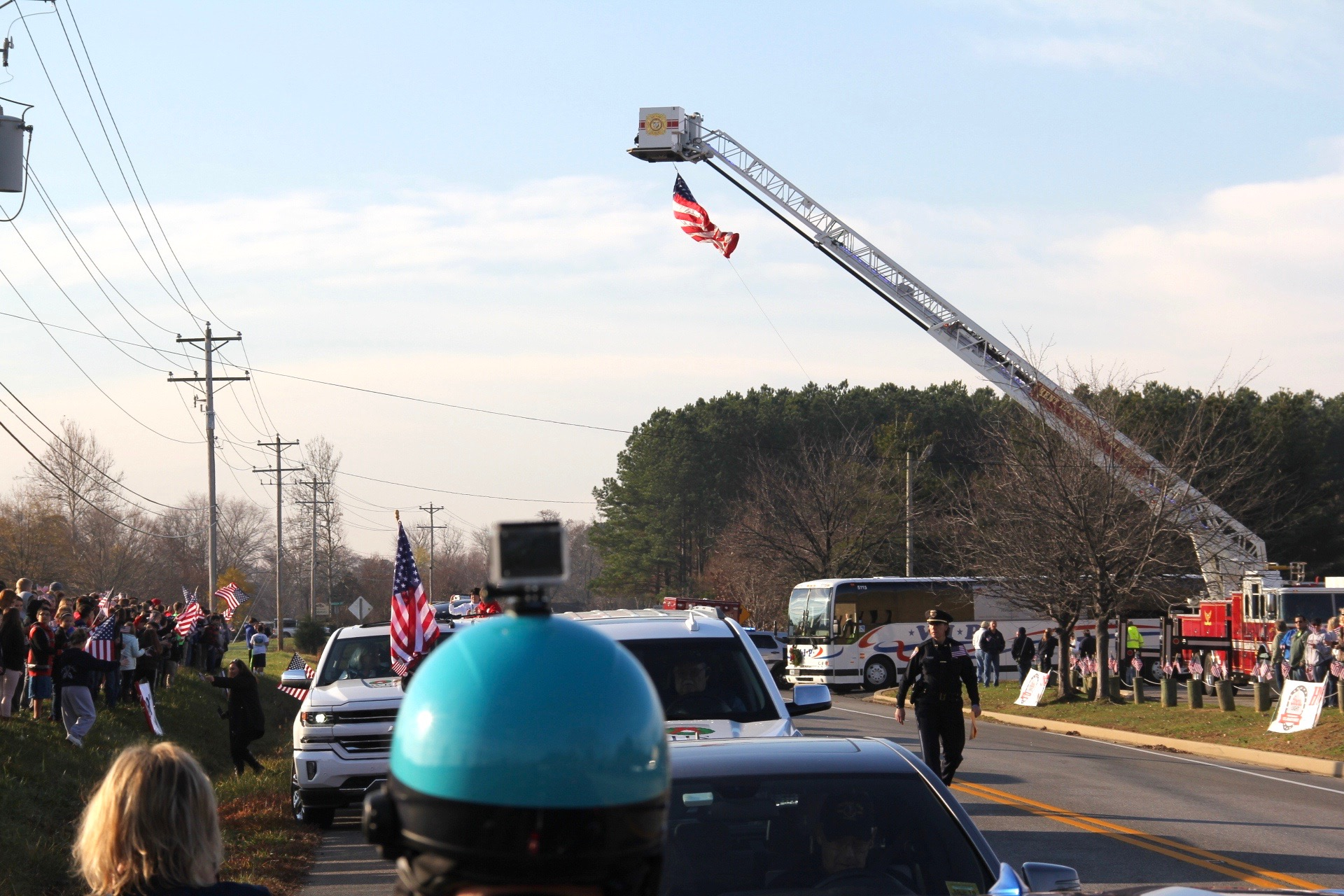 "2015 Wreaths Across America Escort to Arlington National Cemetery prepares to depart Stevensville, MD as students lined the banks with their American flags and thank you messages shouting, ""USA, USA, USA!"""