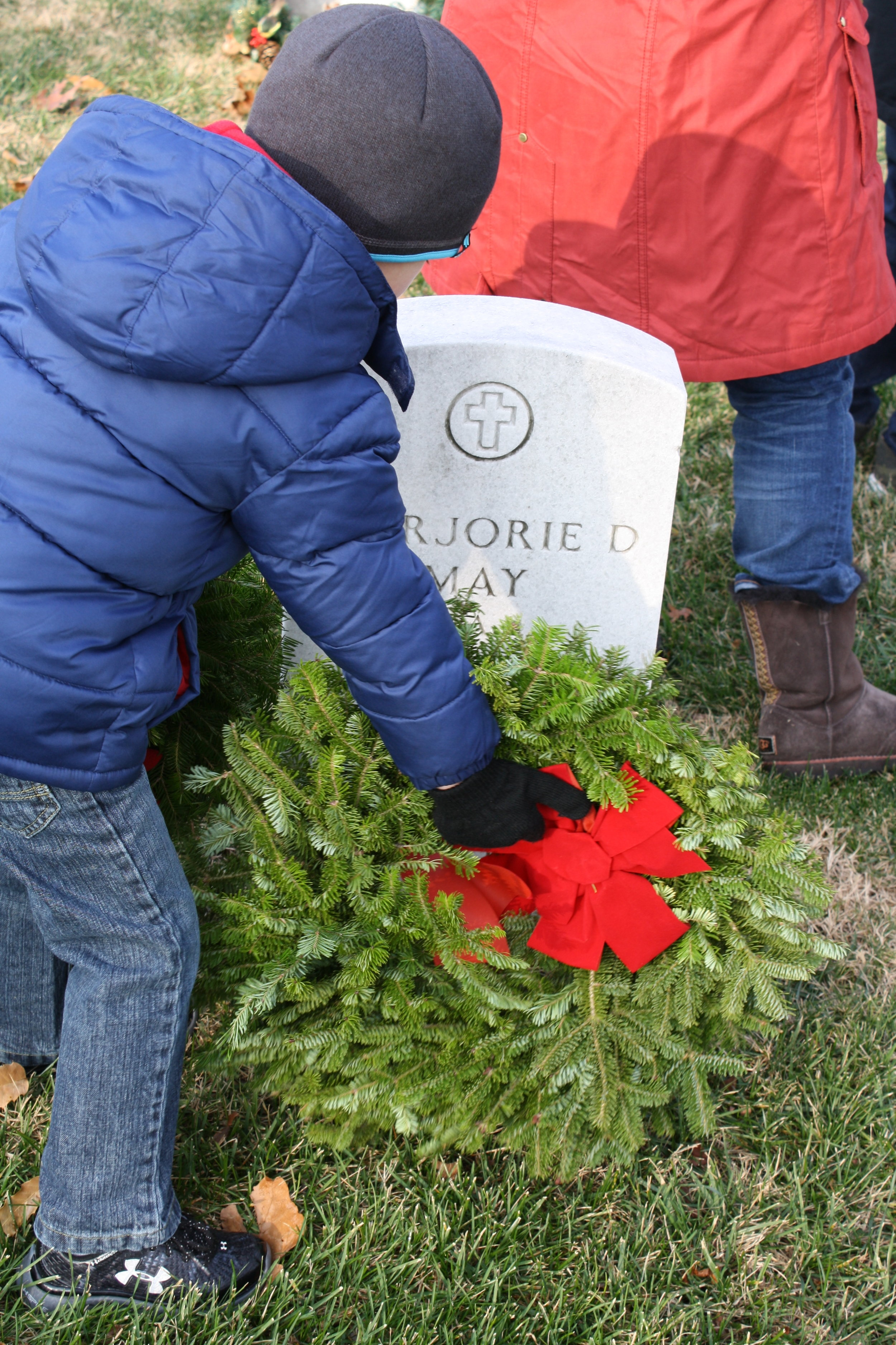 Christopher Hamilton places a remembrance wreath in Arlington National Cemetery during National Wreaths Across America Day, 2014.