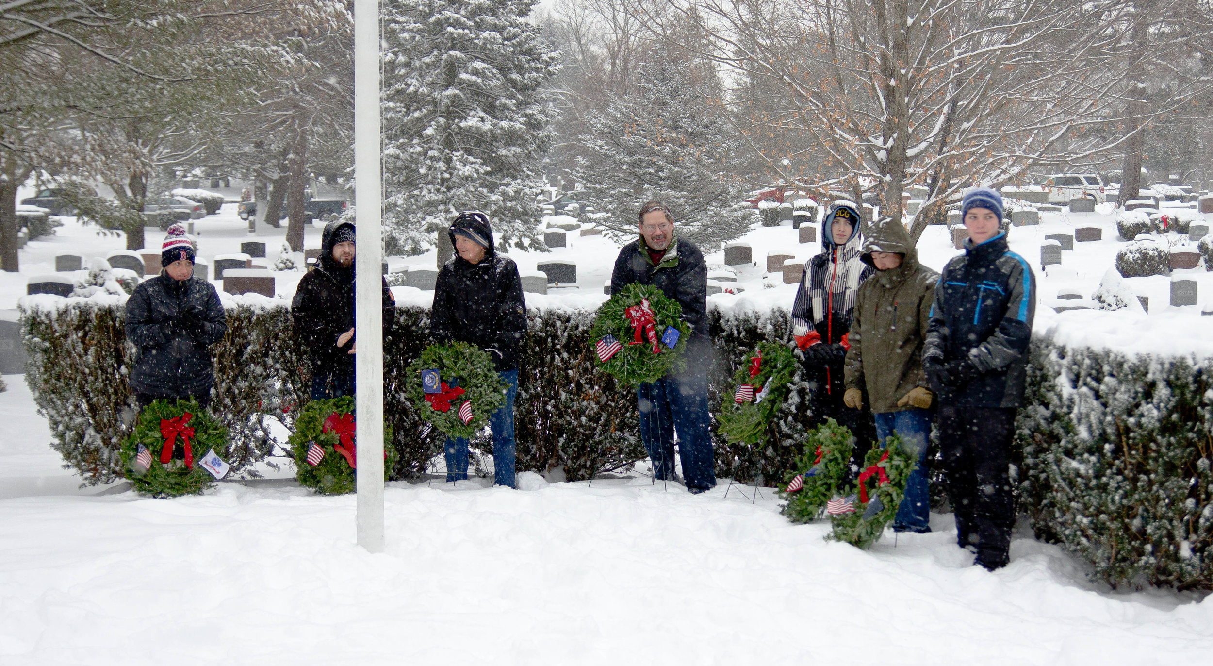 Despite a heavy snowfall volunteers participate in the National Wreaths Across America Day ceremony at Fairview Cemetery in Westford, Massachusetts.