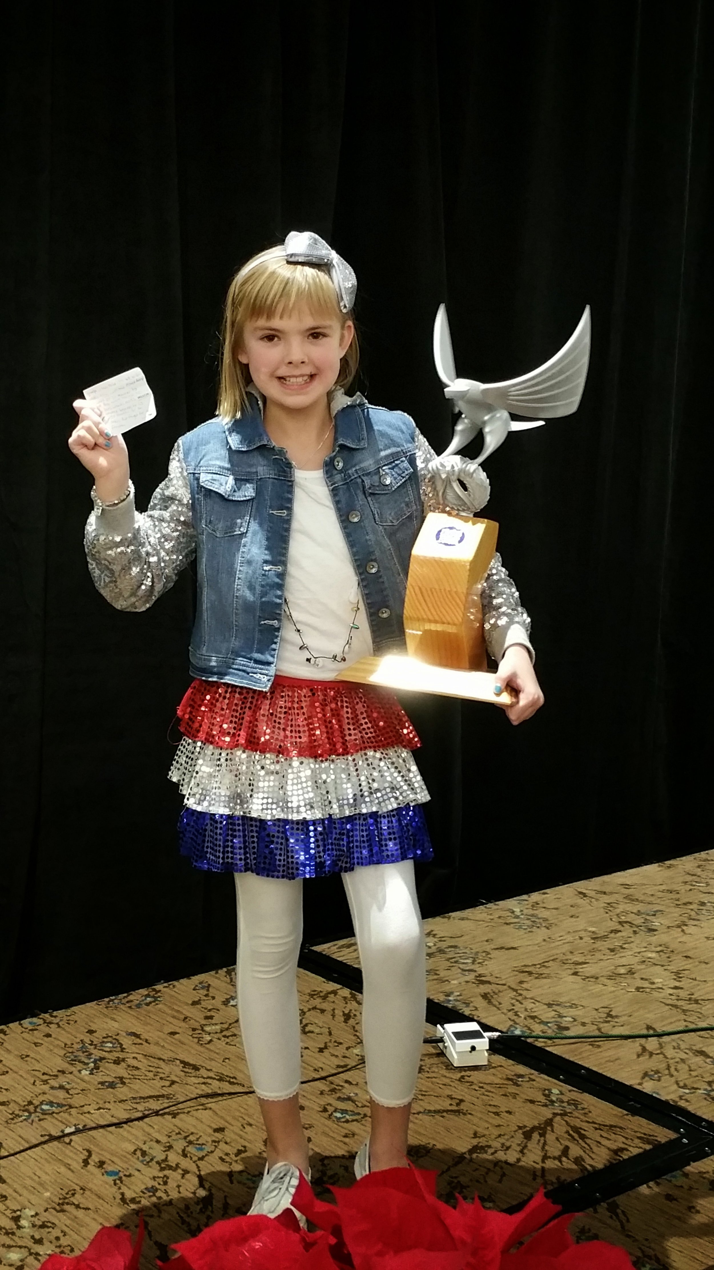 Ella is seen here in 2014 after accepting the inaugural Wreaths Across America/James Prout Spirit of Giving Award on behalf of her grandfather, Bob Baylor. He passed in 2015 and Ella continues to honor his memory.
