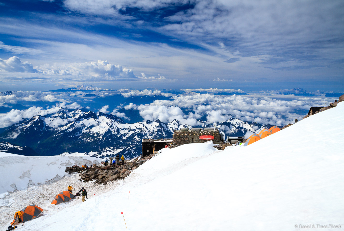 View from Camp Muir: the main shelter/hut and climbers' tents with Mount Adams right below the clouds
