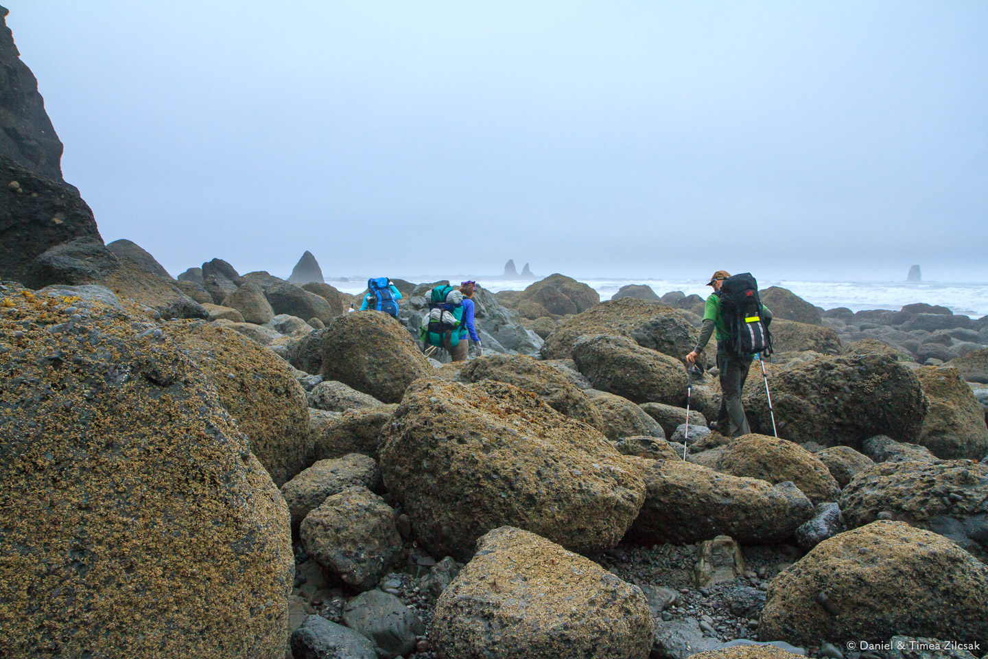 Hiking across a bolder field at Jefferson Cove on the South Coas