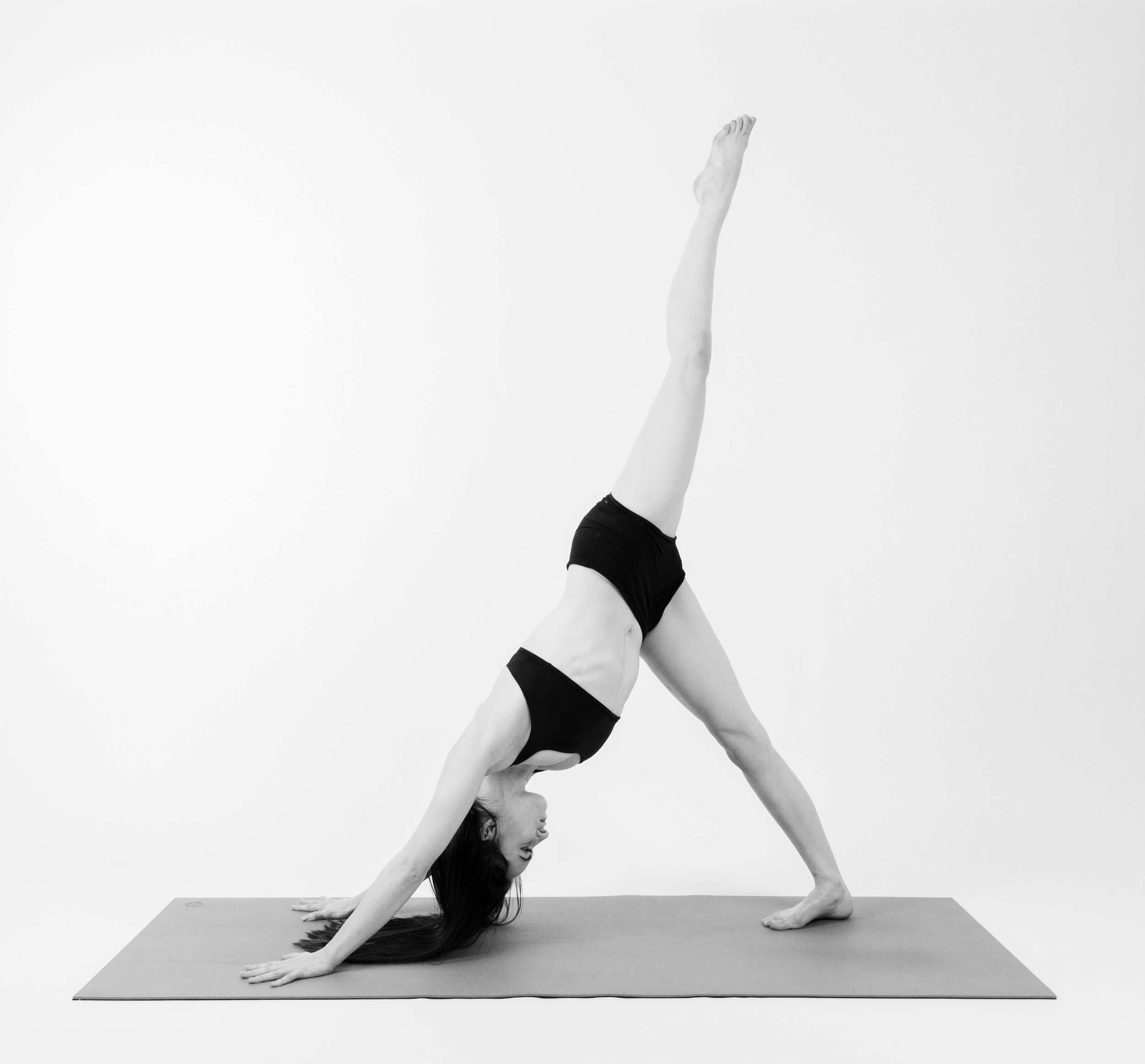 ONE FOOT DOWNWARD FACING DOG    Tuck your toes under, lift your hips up and back and gaze at your navel. Take a deep inhale and extend your right leg up behind you.