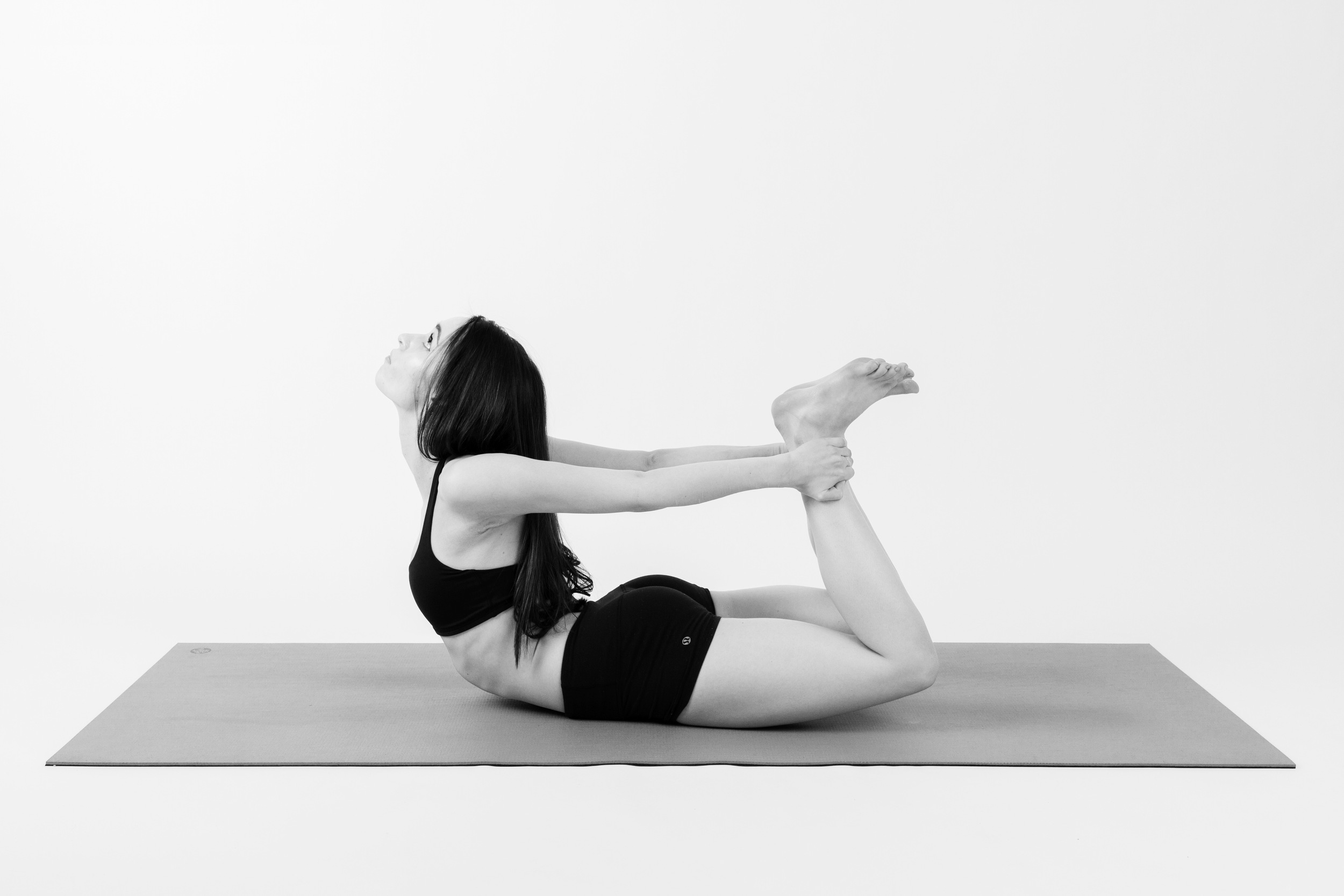 BOW    Start to bend your knees back behind you. Reach back with both hands and grab a hold of your ankles, or the outsides of your feet. Try extending just a little higher, lift your chest and feet as you look up.
