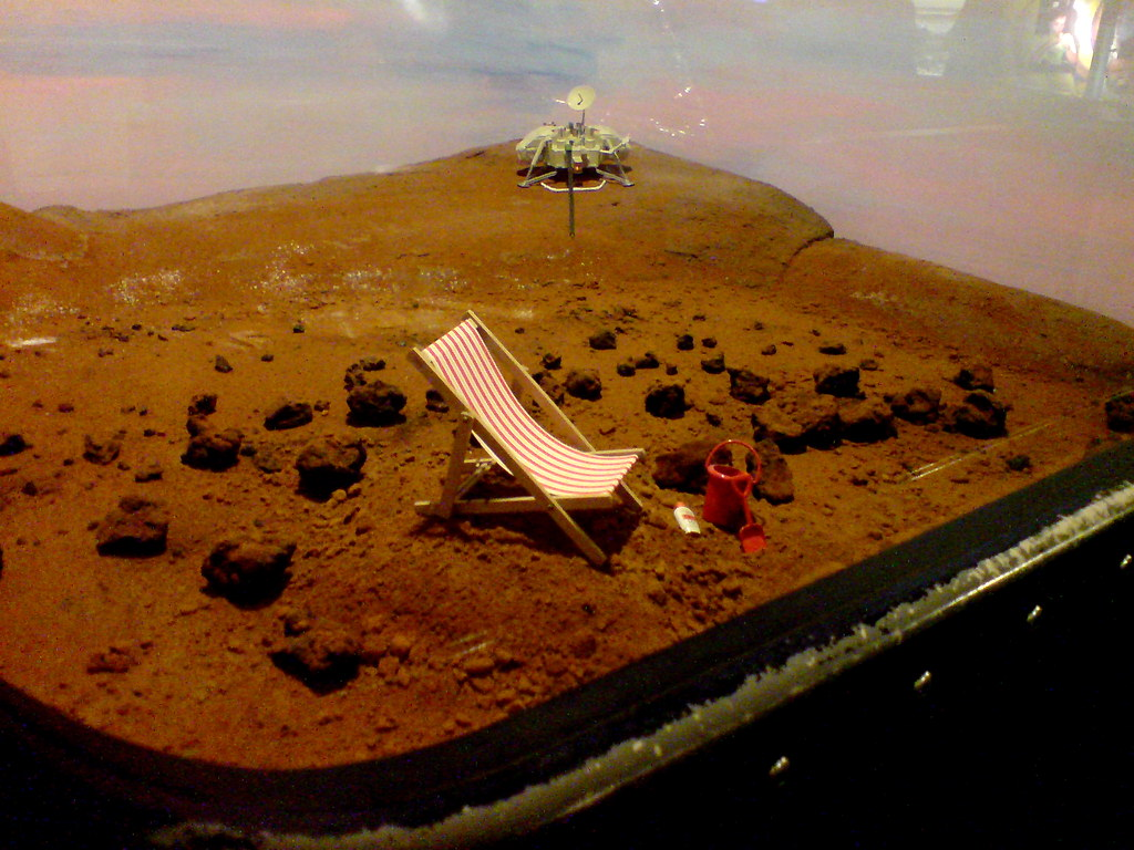 At the Science Museum, London, a diorama of a deck chair, bucket, spade, and suncream with a planetary lander in the background suggest humanity's future on Mars. Image credit: garrettc