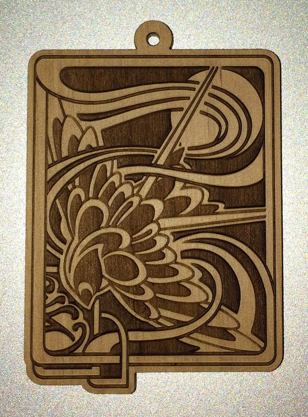 """Espi.  Pendant . 2014 - etching on wood, 6"""" x 3""""."""
