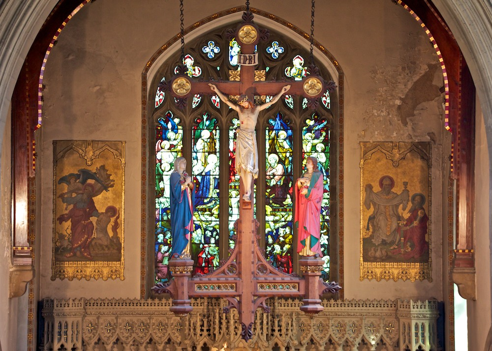 The hanging rood and stained glass windows with murals on either side