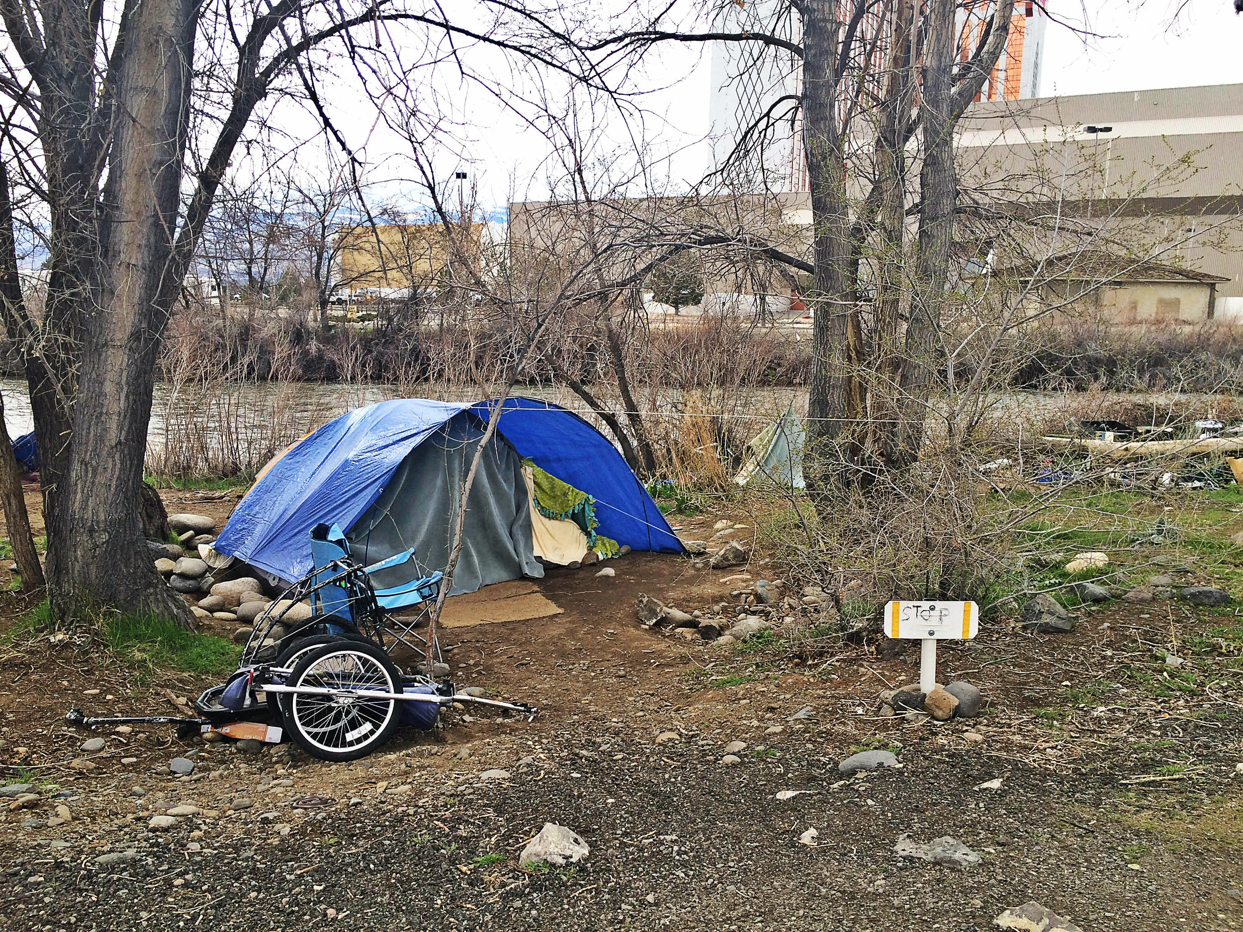 One of the tents in this encampment has a sign reading 'stop' at its entrance. Photo by Monica Gomez