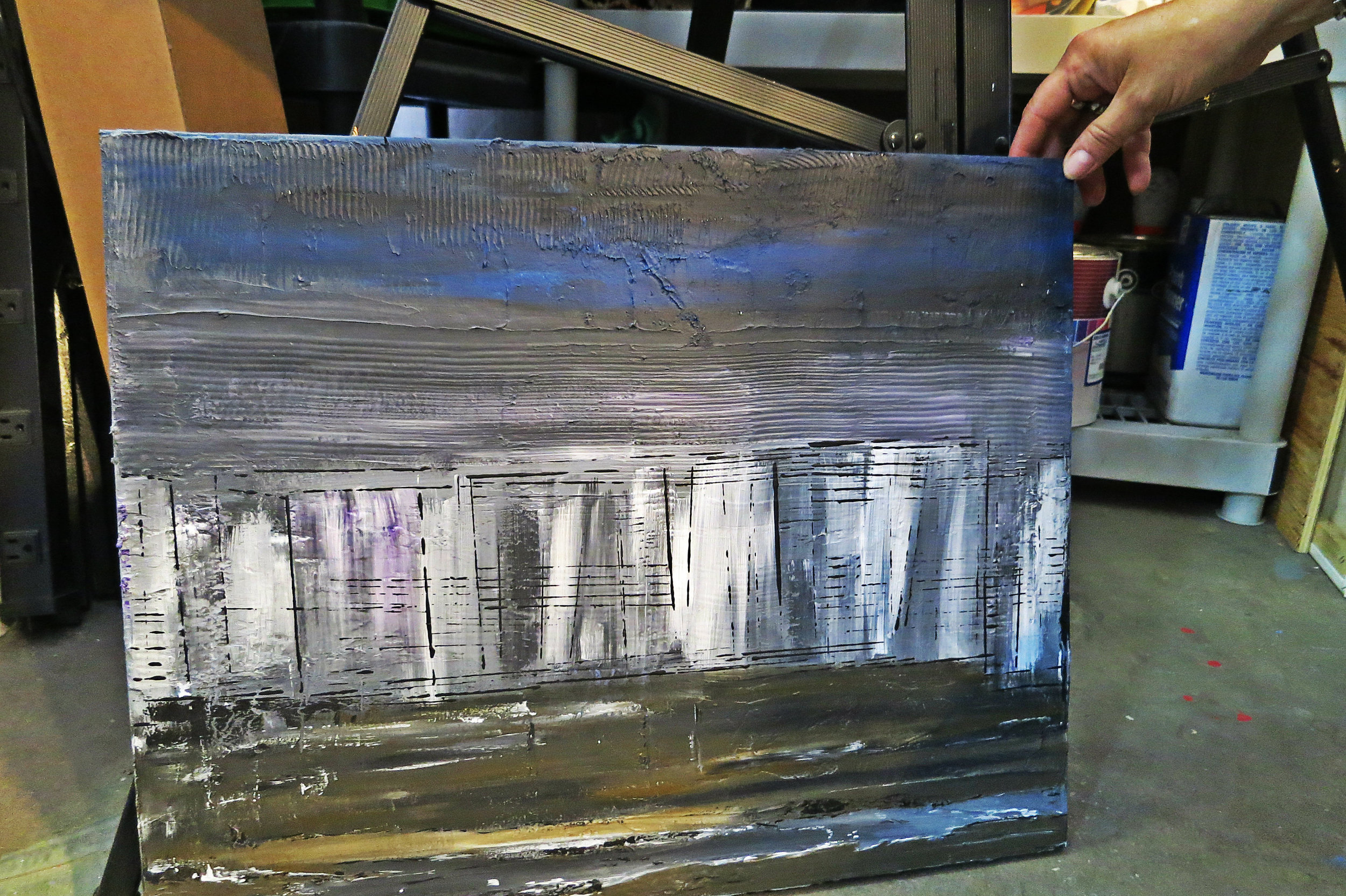 """Another work in progress: """"I have an idea here with charcoal ash, I want to create smog. But then down here, I want to create some daisies. It doesn't matter how dark, or gloomy or smoggy it is; there's a light, there's hope, there's a ray of sunshine."""""""