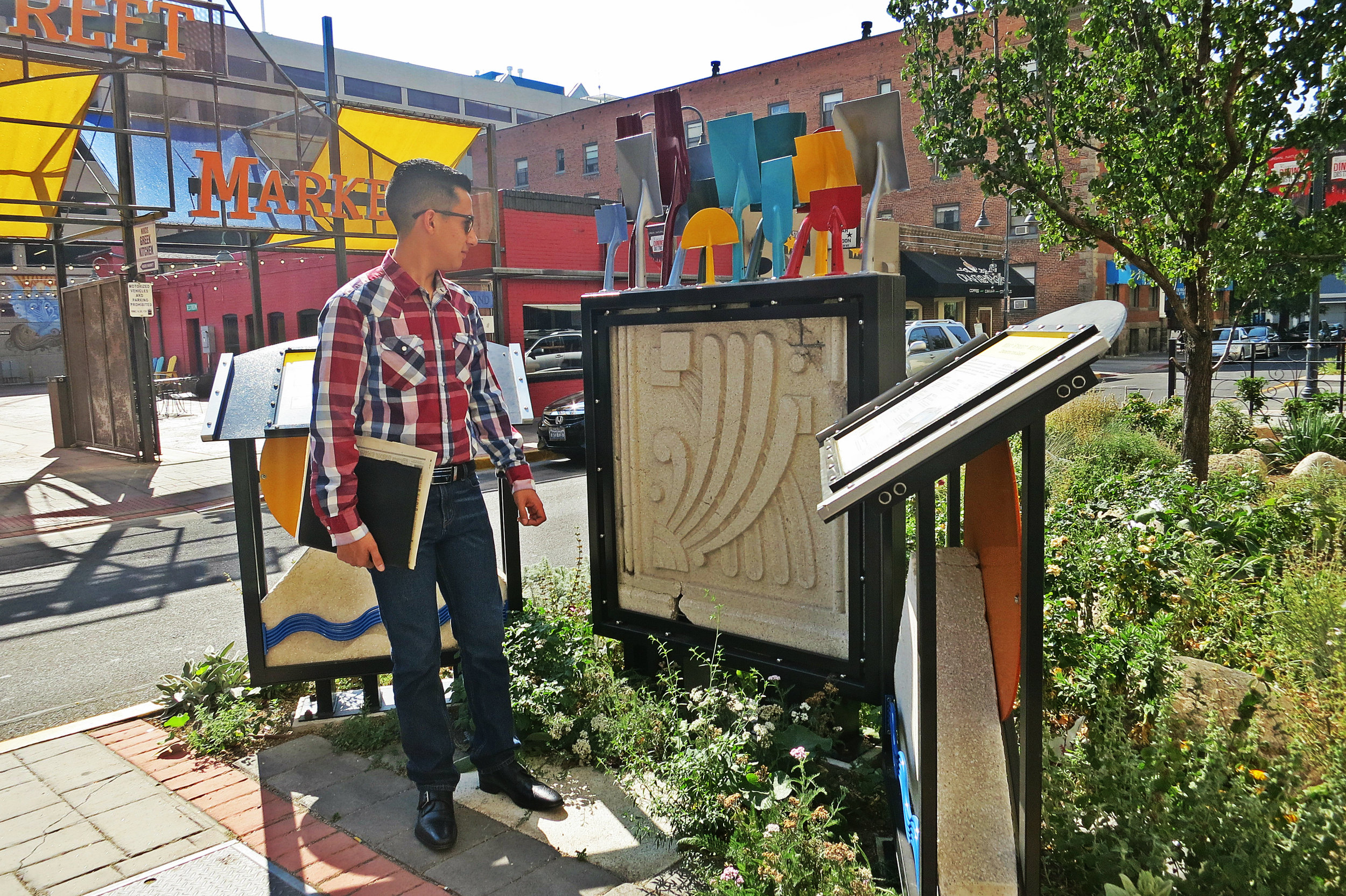 """Hagen stands next to a small tribute to old buildings on West Street, which includes a broken terra cotta tile salvaged from the Mapes. """"I think it's awesome. I wish it was closer. It would have been cool if they would have incorporated this into the new downtown plaza where the Mapes used to be."""""""