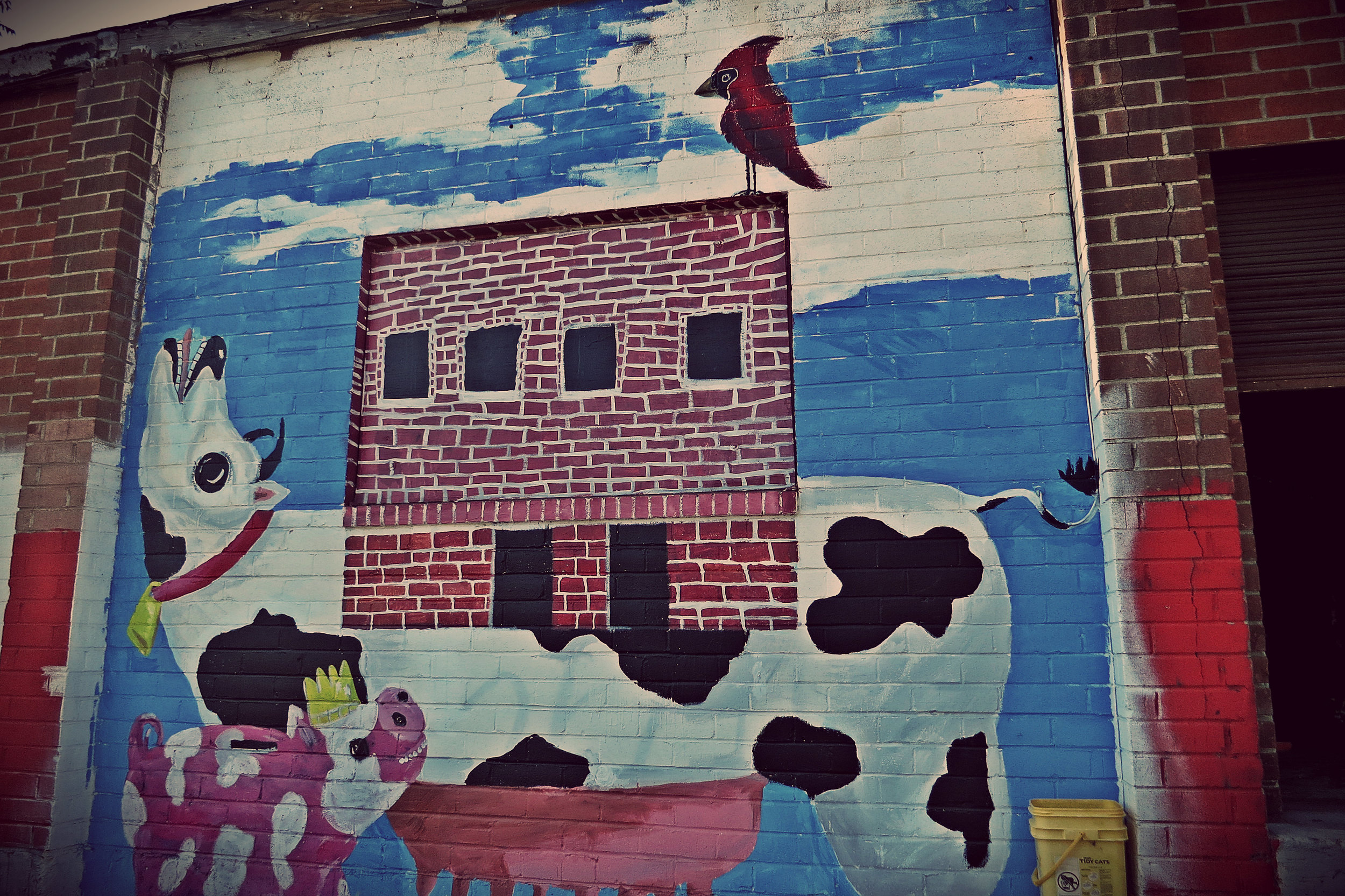 """""""This is acrylic on brick. The cash cow's got our building on his back, with a little bird of hope at the top."""""""