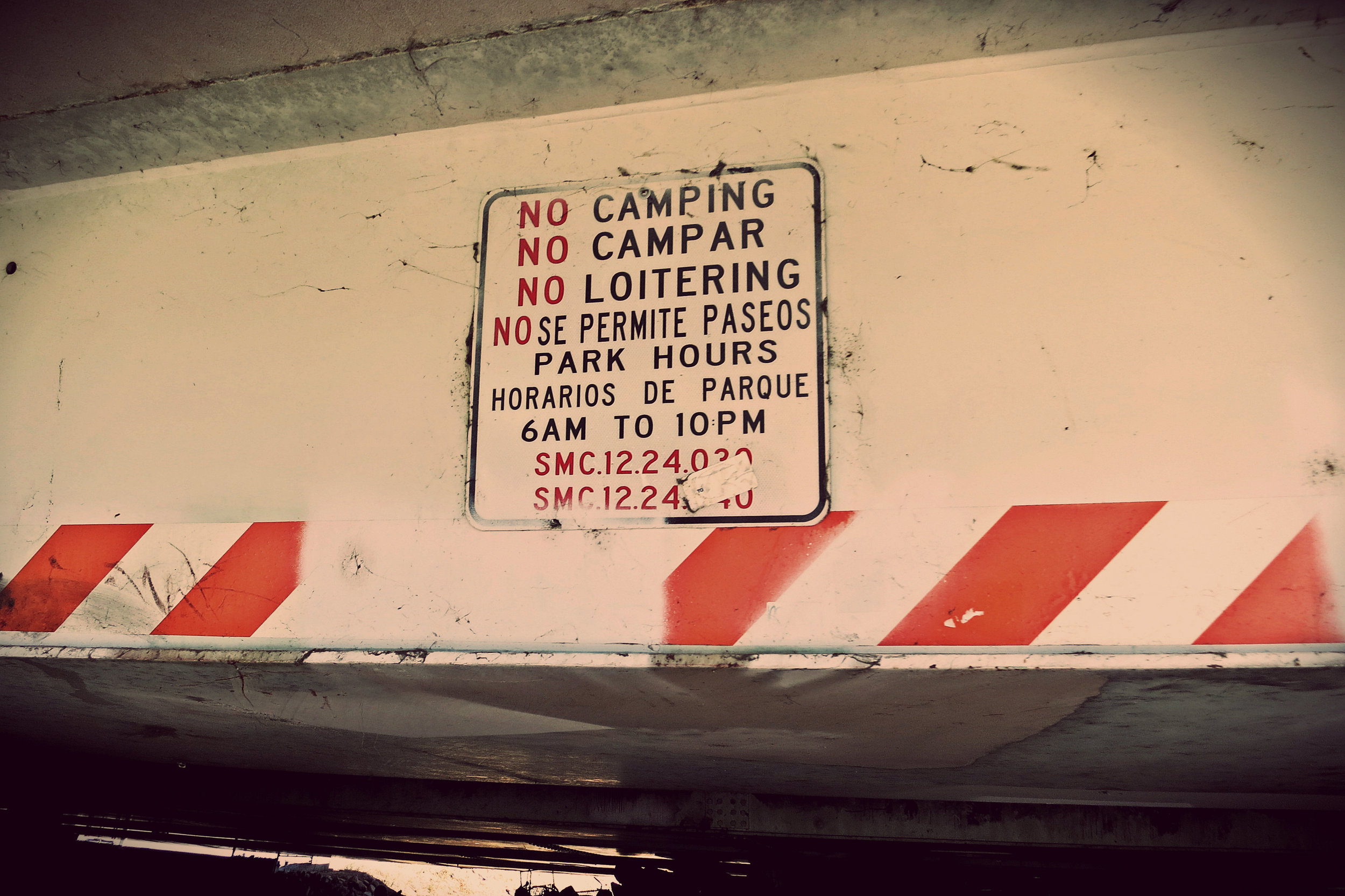 This sign on an overpass to the river path makes people camping there, out of necessity, fear every day they might be kicked out.