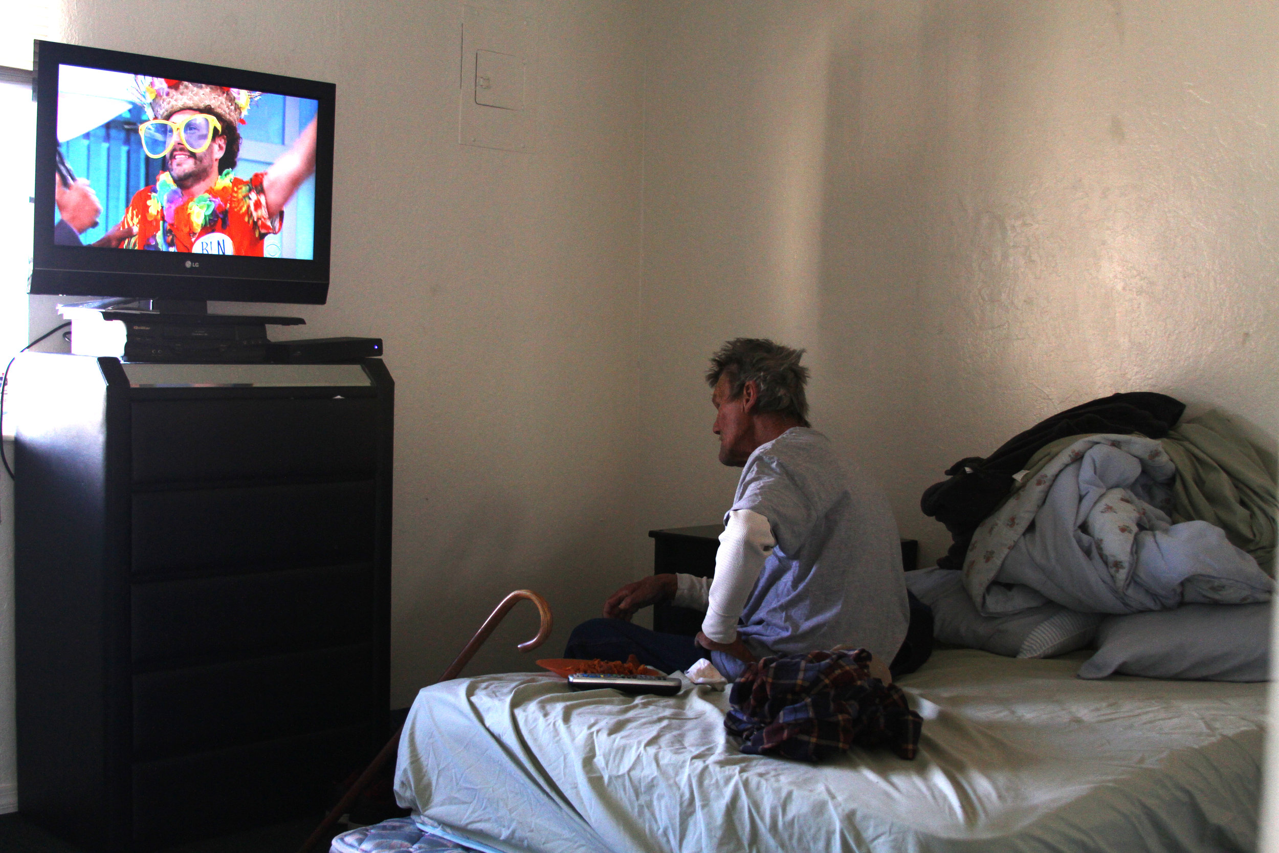 Doug watches trippy TV in his new room, found and furnished by volunteers.