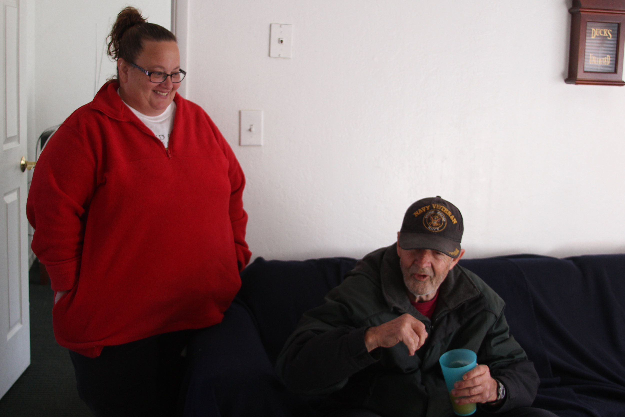 Michelle Mello and Steve, a veteran, share a laugh in the apartment where Doug now lives.