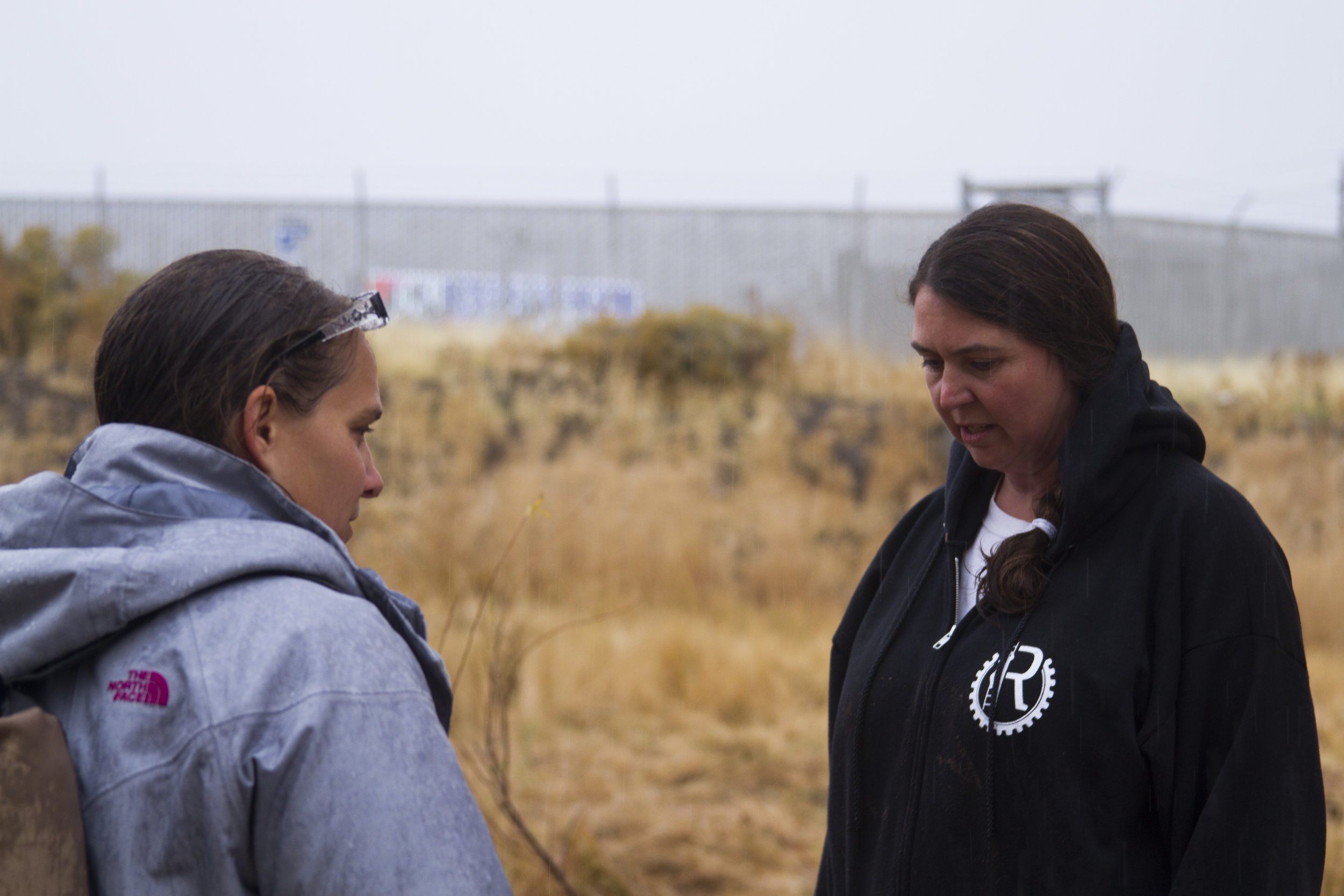 Katie Colling (left) and Jennifer Cassady (right), both with the local Reno group known by its acronym RISE, discuss the homeless encampment area previously protected by brush.