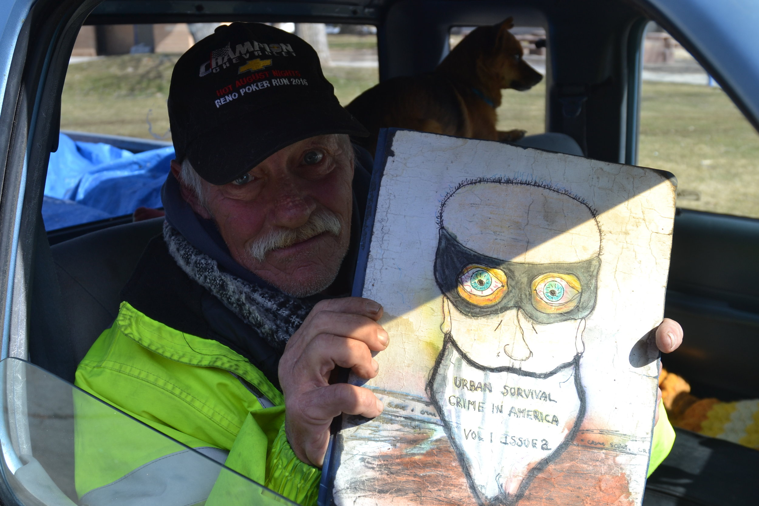 Jimbo sometimes stays in Deb's truck.  He shows one of the illustrated manifestos he's been working on. Photo by Jacob Jacoby for Our Town Reno