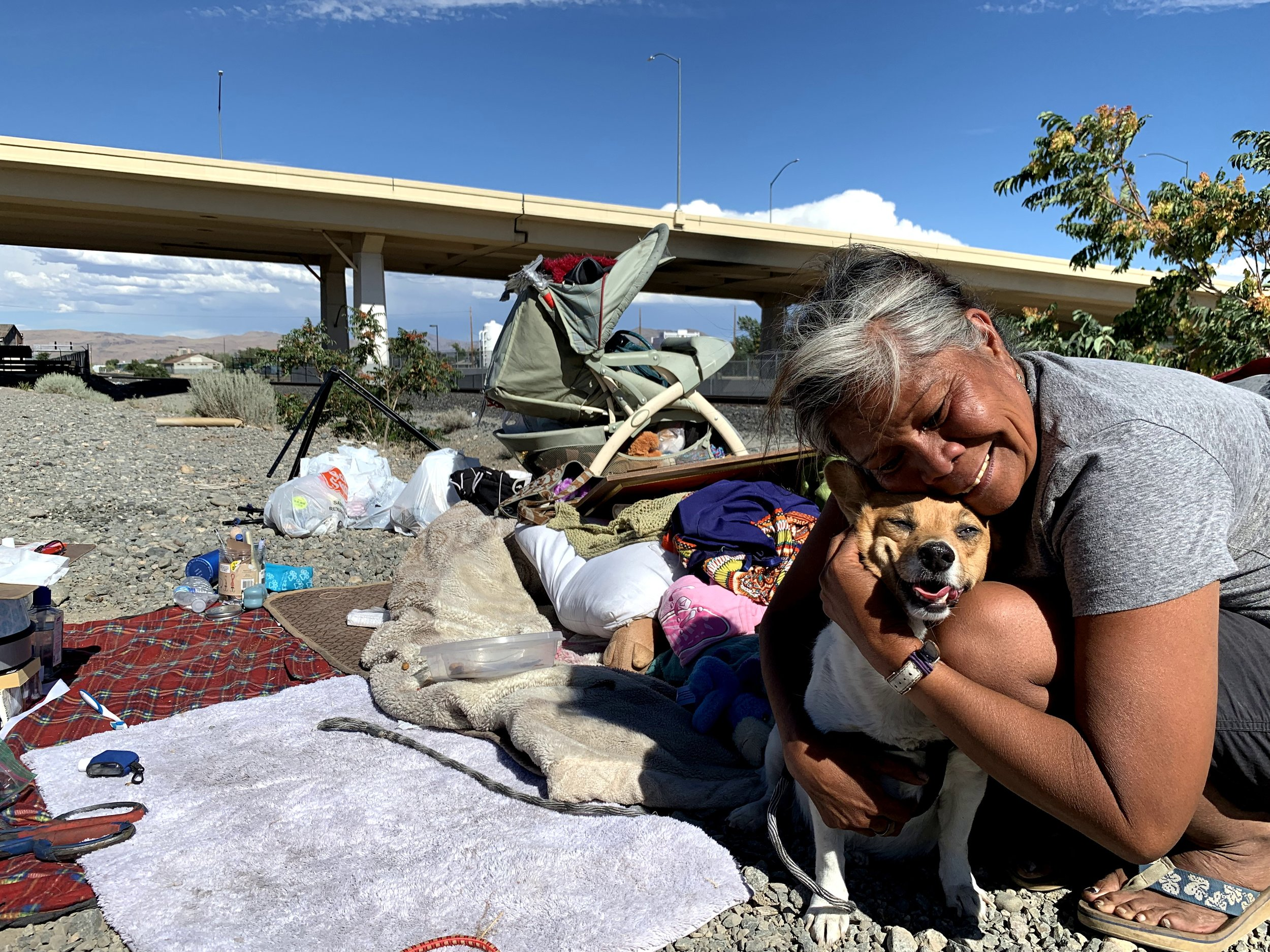 Marilou Gallegos cuddles her dog, Nikita, who she's had for six years. She doesn't go far from her belongings in fear of them getting stolen again or thrown away.