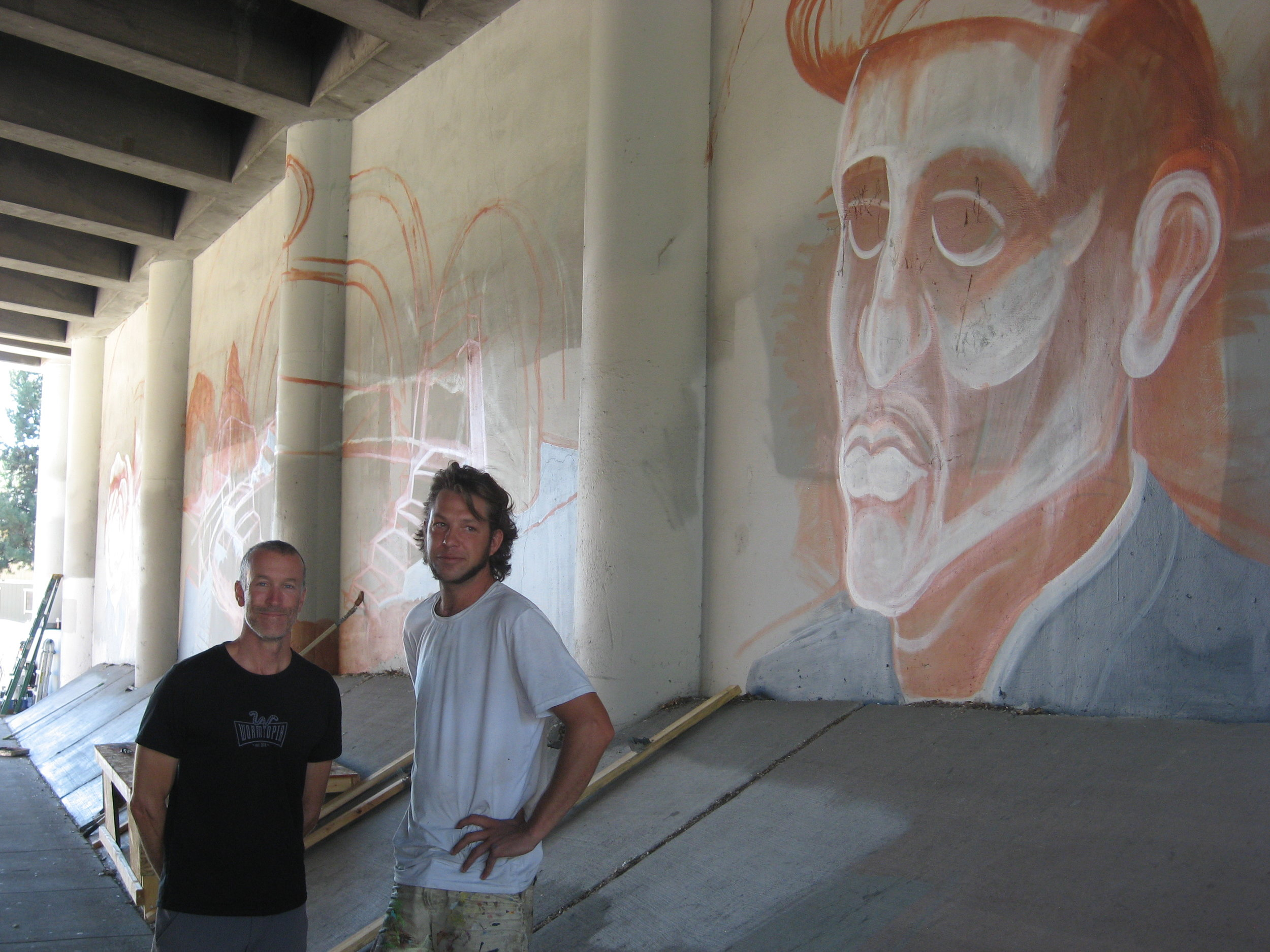 Kyle Chandler-Isacksen (left) and local artist Asa Kennedy are helping the Two Hands Collective complete a giant Day of the Dead mural inside the 395/Wedekind Road underpass. The project started later than expected, and now the aim is to finish by the end of October.