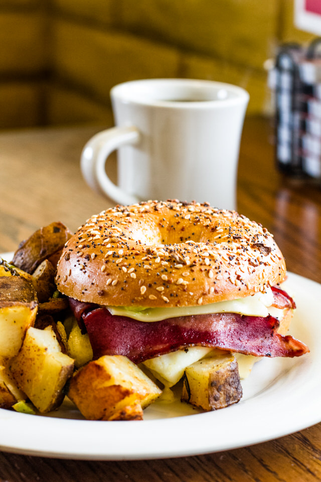 Turkey Bacon Bagel Sandwich - Turkey Bacon, egg whites, pepper jack cheese, & avocado mayo on an everything bagel. Served with a choice of a breakfast side (hash browns, home fries, grits, coleslaw, or tomato slices).Upgrade Sides: +$1.00 (cup of fruit, cottage cheese, salad, or black beans).