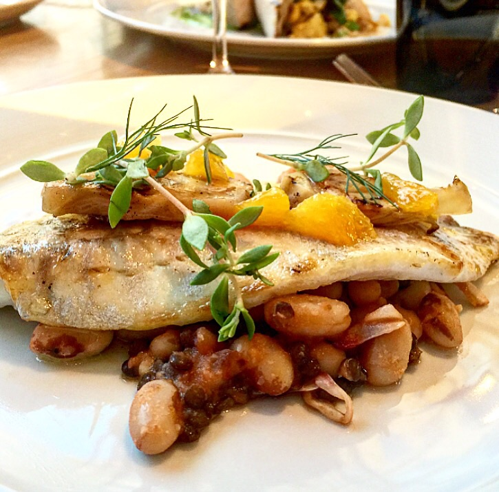 Perfectly cooked sea bass with yellow eye beans, fennel and preserved tomatoes.
