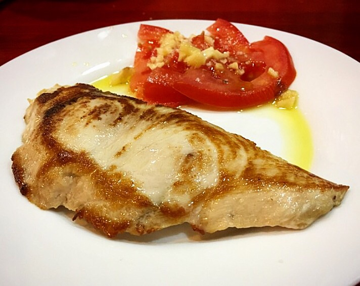 A bit of fish with garlicky, juicy tomatoes makes for a delicious snack in Jerez