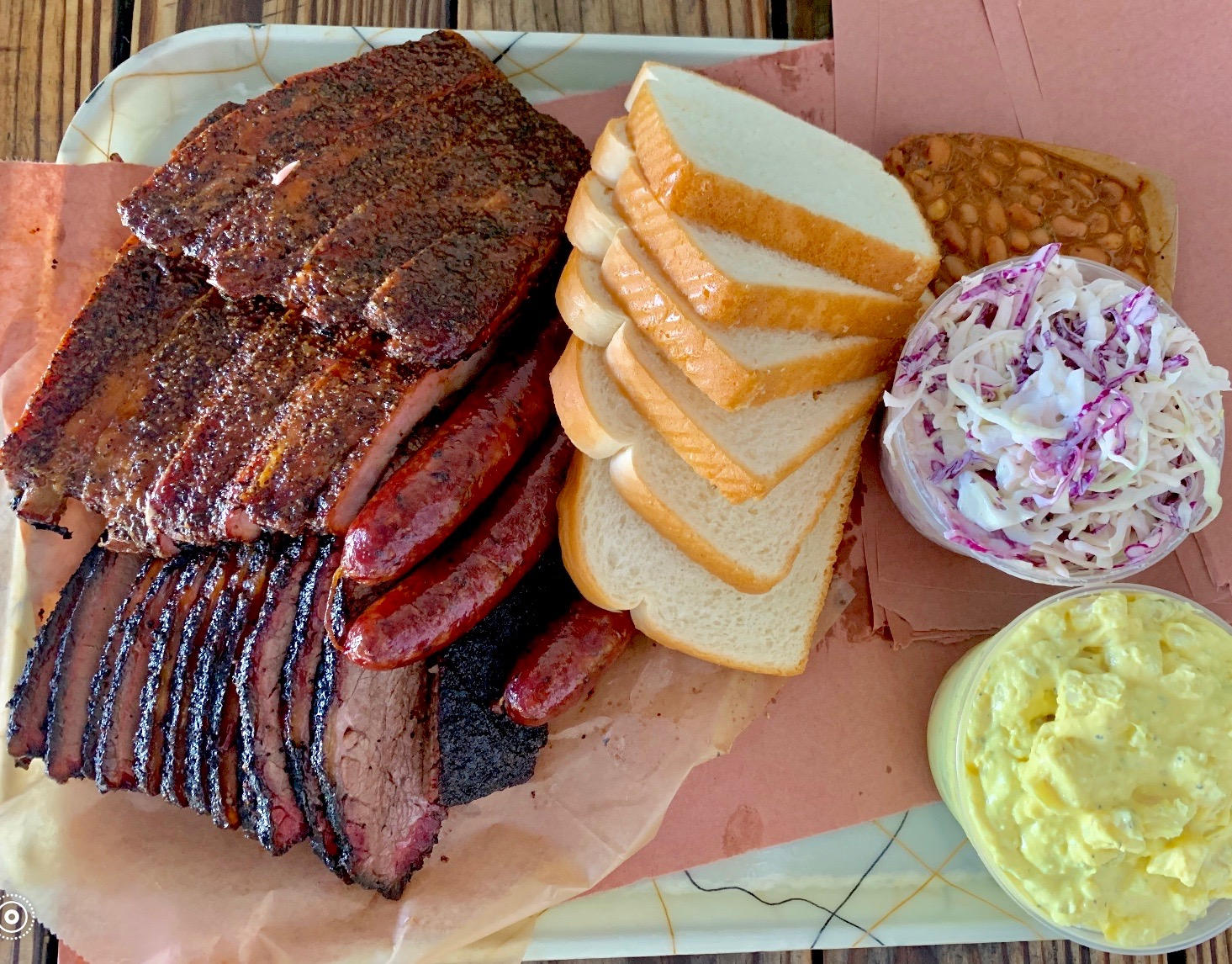 Franklin Barbecue's Brisket, sausage, and pork ribs with baked beans, cole slaw and potato salad — worth waiting hours for? You bet it is!