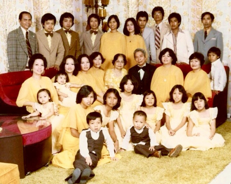 Papa (standing far left, checkered jacket) / Mama (seated far left with my youngest sister Ricci) / Ate Cheryl (standing fifth from Papa) / Tommy (seated at the couch-arm far right) / MJ and Ces (seated at the floor directly in front of Mama / Lolo & Lola (center) / Uncles and Aunts and Cousins shown / + The only guy with spectacles, afro hairdo, organic beach tan, clown Pierre Cardin tie, and super-high waist slacks:  In Search of Identity Me.   Early 70's