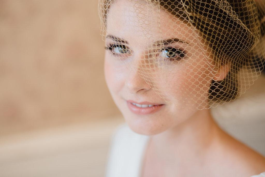 natürliches Brautstyling mit goldenem Netz Fascinator und künstlichen Wimpern