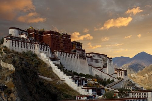 """The Potala Palace, home of the Dalai Lama, stands at an angle on a hilltop during a beautiful sunset in Lhasa, Tibet"""