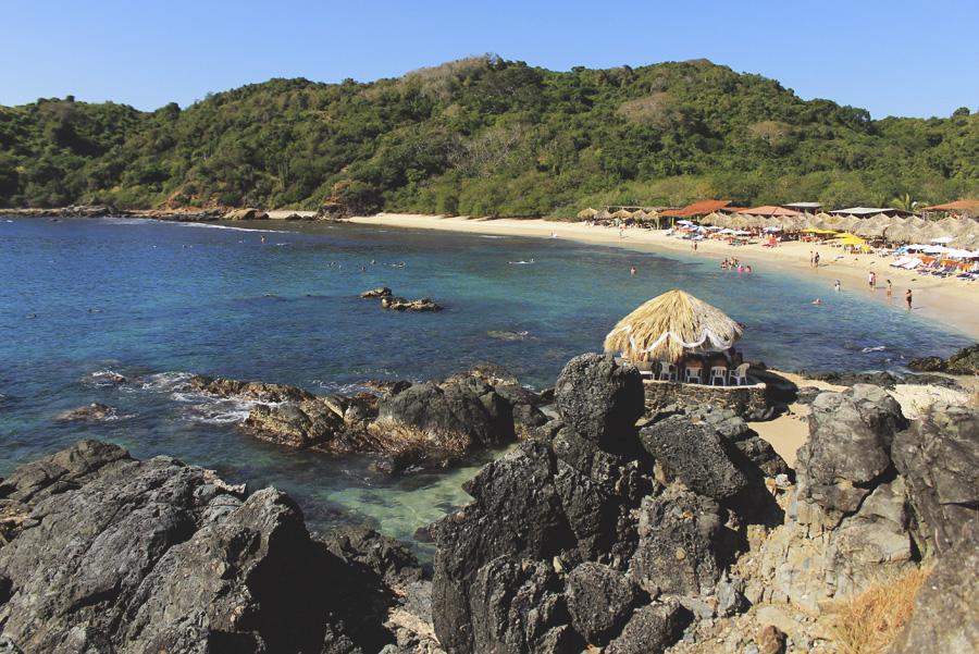 beach grass huts ocean rocks mexico ixtapa zihuatenejo