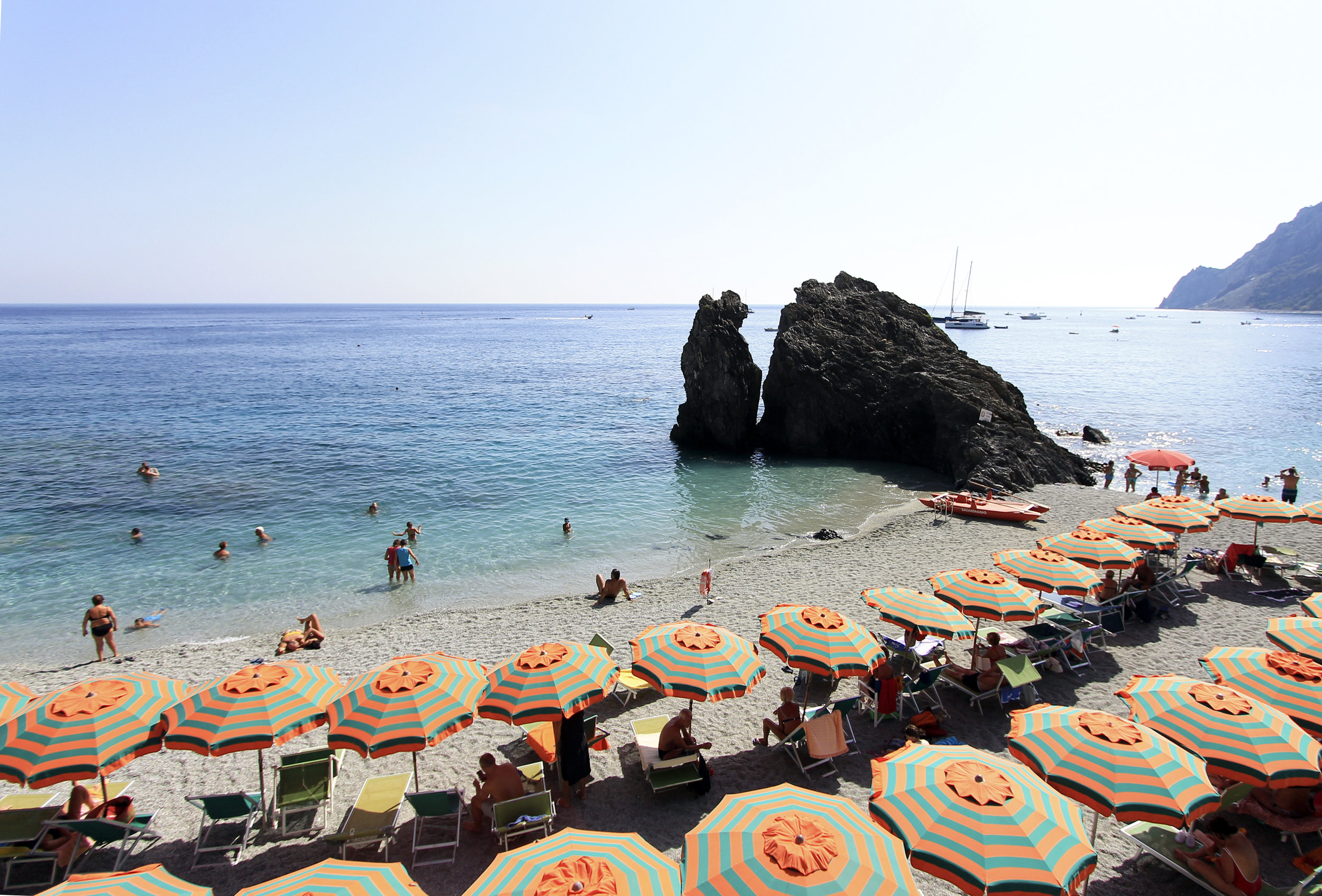 Monterosso striped umbrellas beach chairs rock sea.jpg