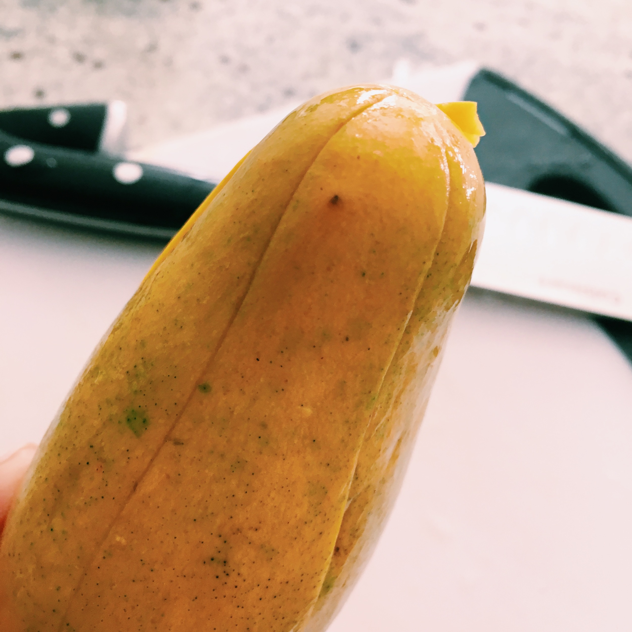 STEP 1: WITH A KNIFE, MAKE VERTICAL INCISIONS FROM THE TOP OF THE MANGO DOWN.