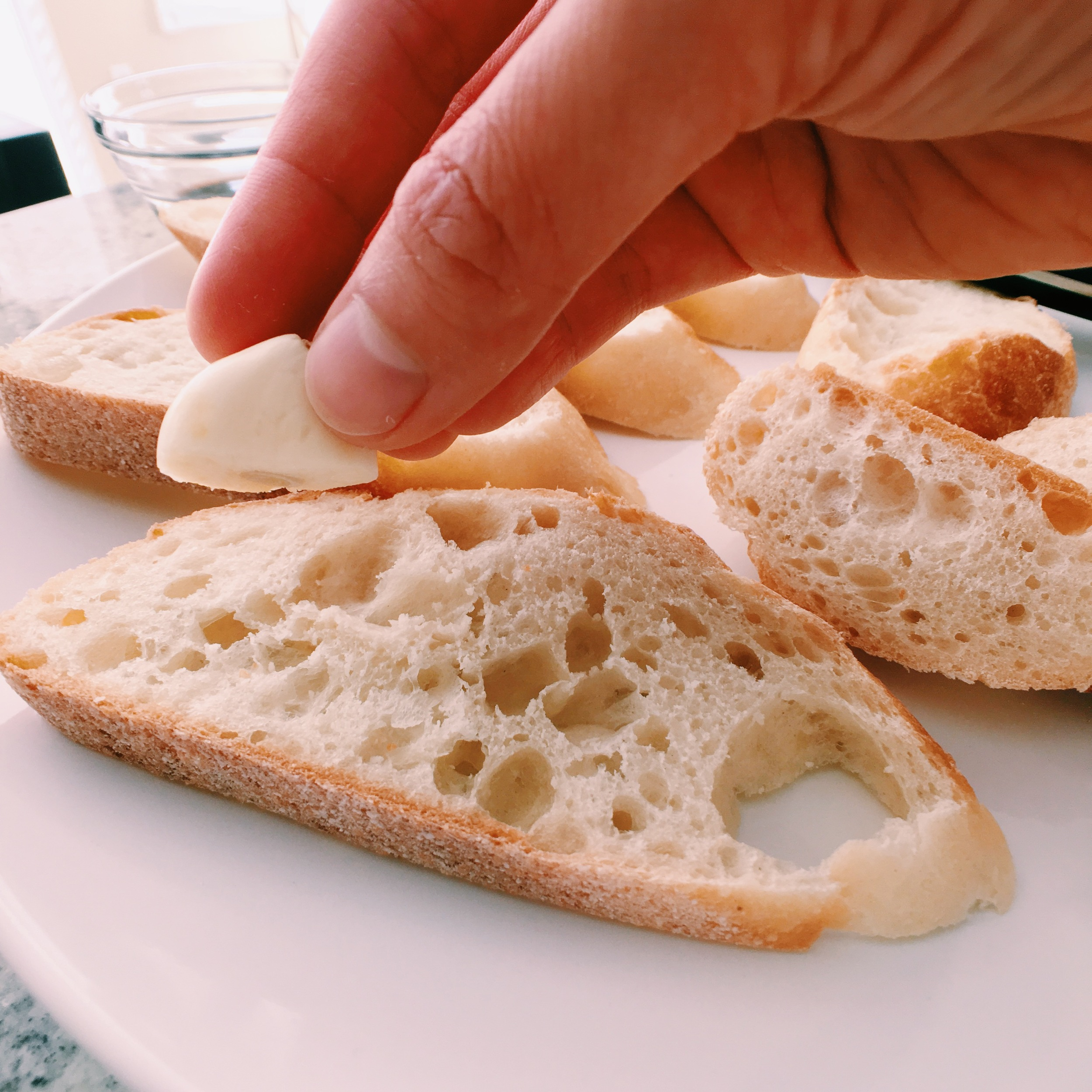 Rubbing garlic onto each baguette slice is the best way to get that garlic flavour into your bruschetta without overpowering it.