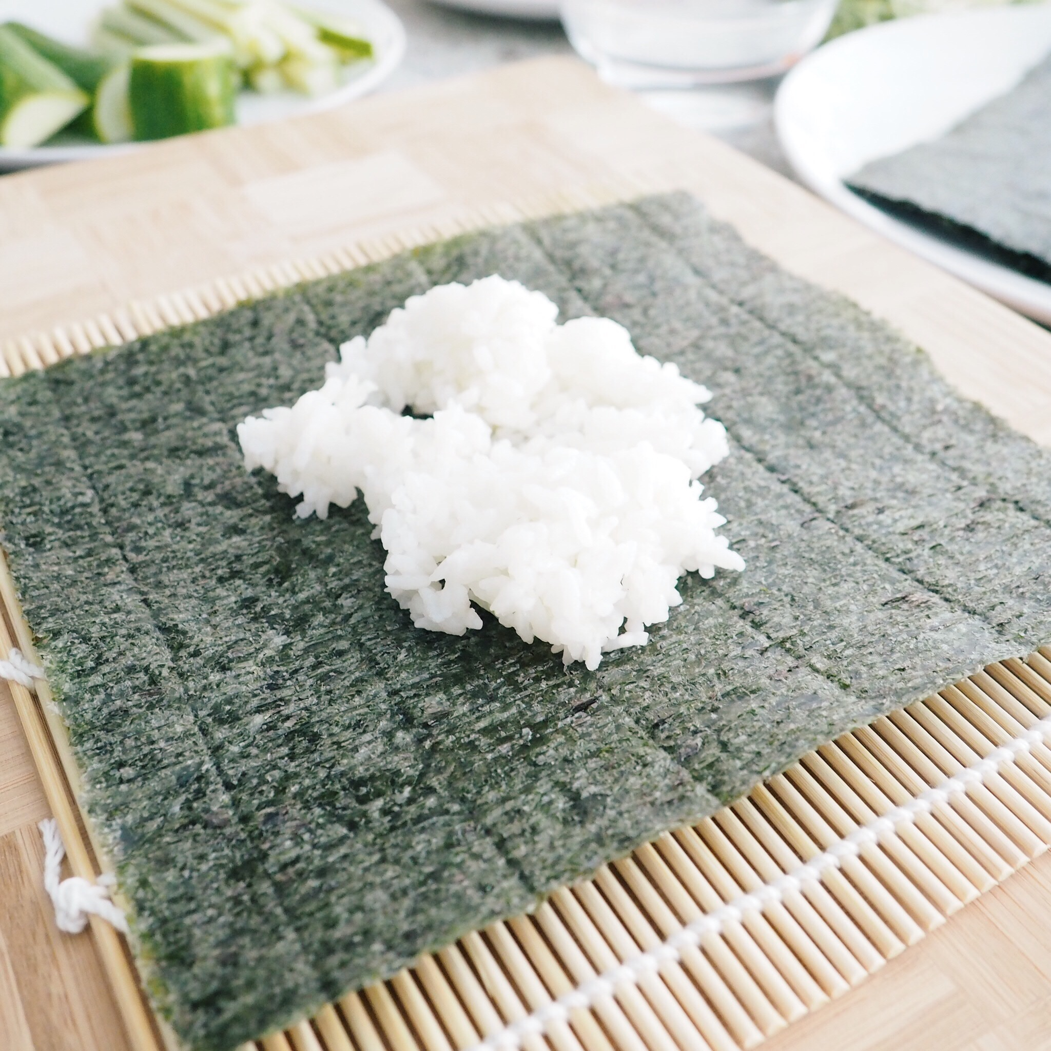 Step 1: Lay nori on bamboo mat roller and add about 1/2 cup of sushi rice