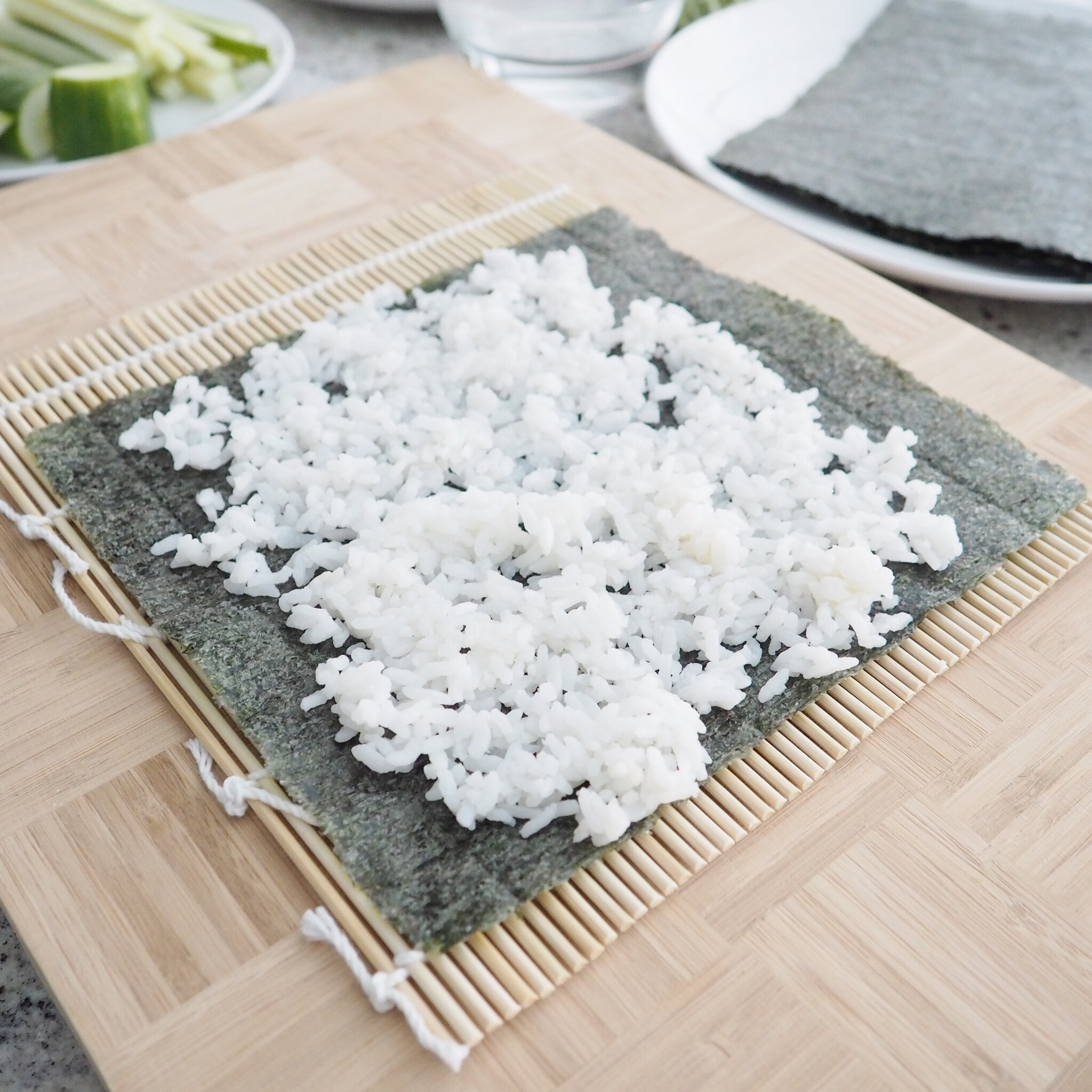Step 2: Spread out sushi rice evenly onto nori, leaving the top and bottom edge.