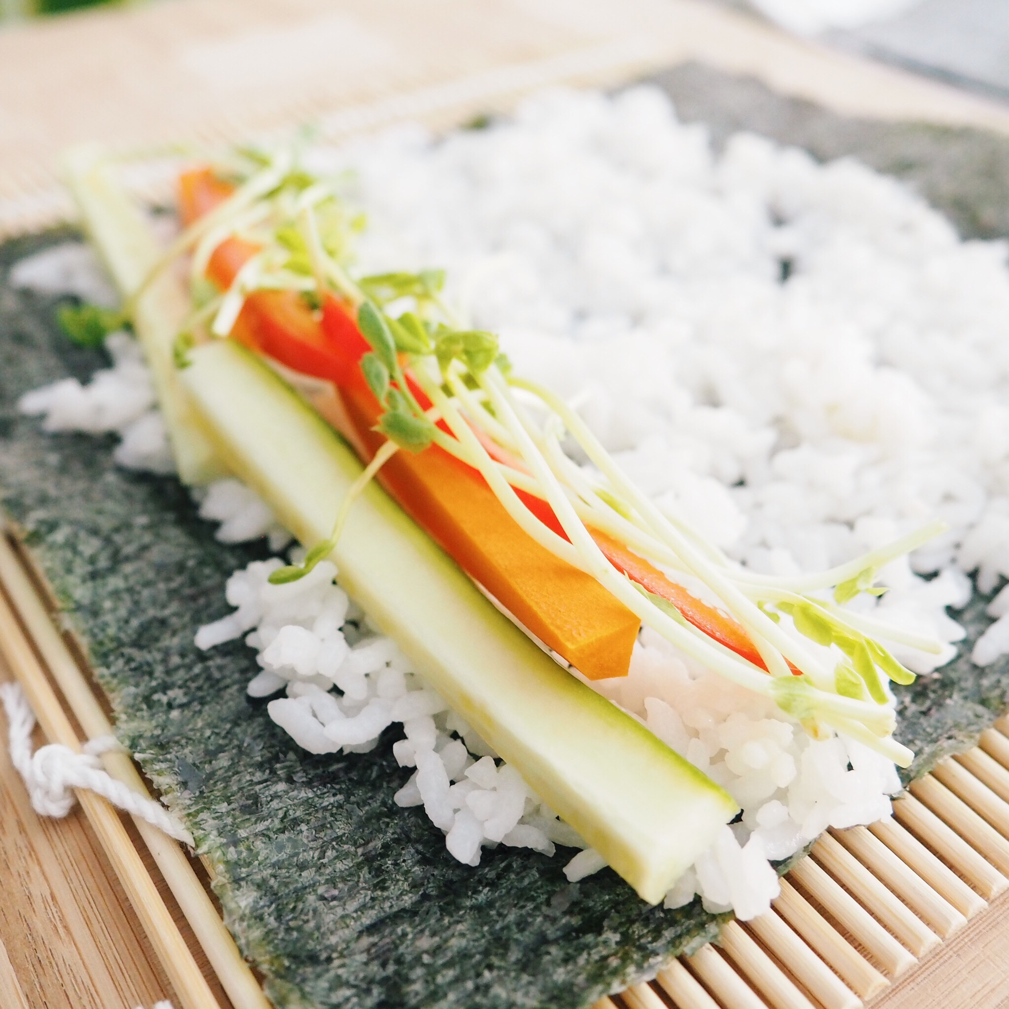 Step 3: At the base of your rice, add a strip of the vegetables.  Try not to overload it or it will be difficult to roll.