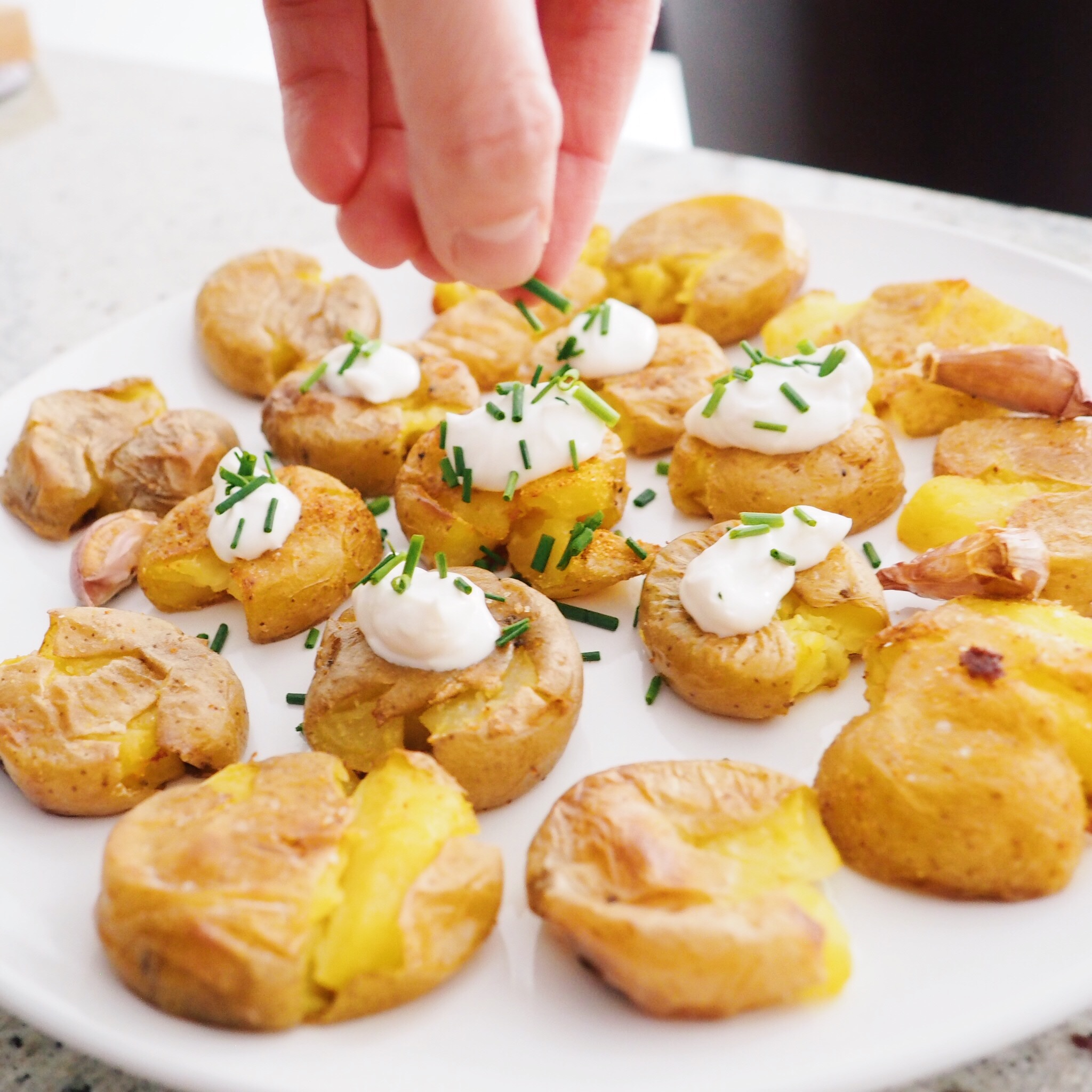 Step 11 - Plate your potatoes, add a dollop of sour cream to each one and garnish with fresh chives. Enjoy!