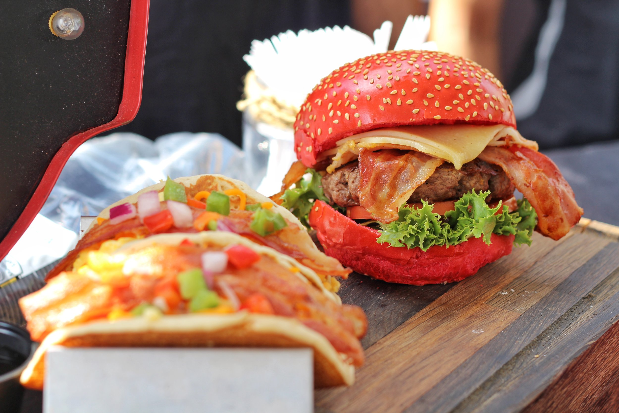 Fluffy buttermilk pancakes stuffed with a combination of fried and scrambled egg, topped with tomato, green pepper, onion and maple bacon strips, drizzled with chipotle syrup + Canada 150 inspired All-Canadian Red Hot Burger.